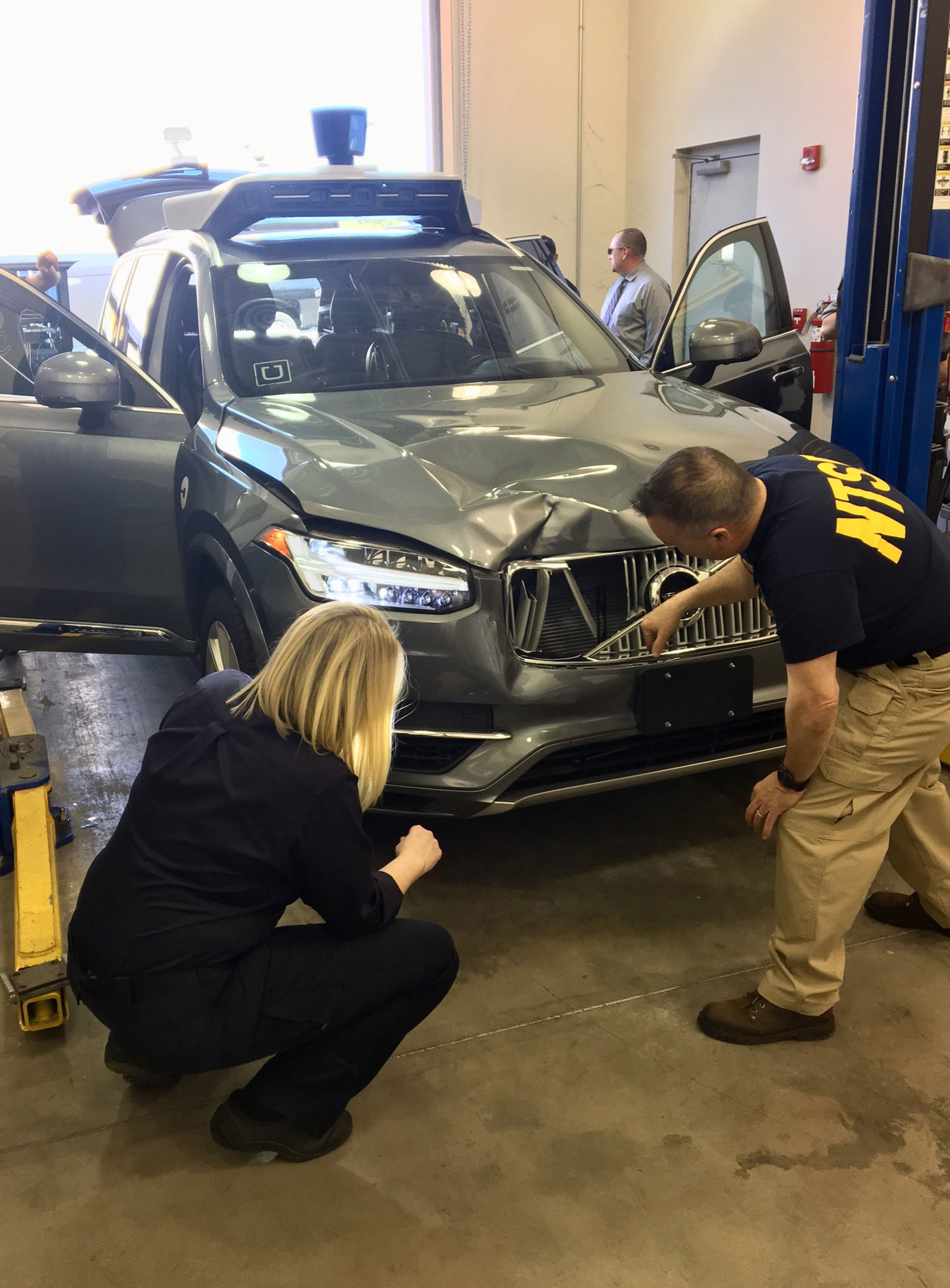 National Transportation Safety Board (NTSB) investigators examine a self-driving Uber vehicle involved in a fatal accident in Tempe, Arizona, U.S., March 20, 2018.