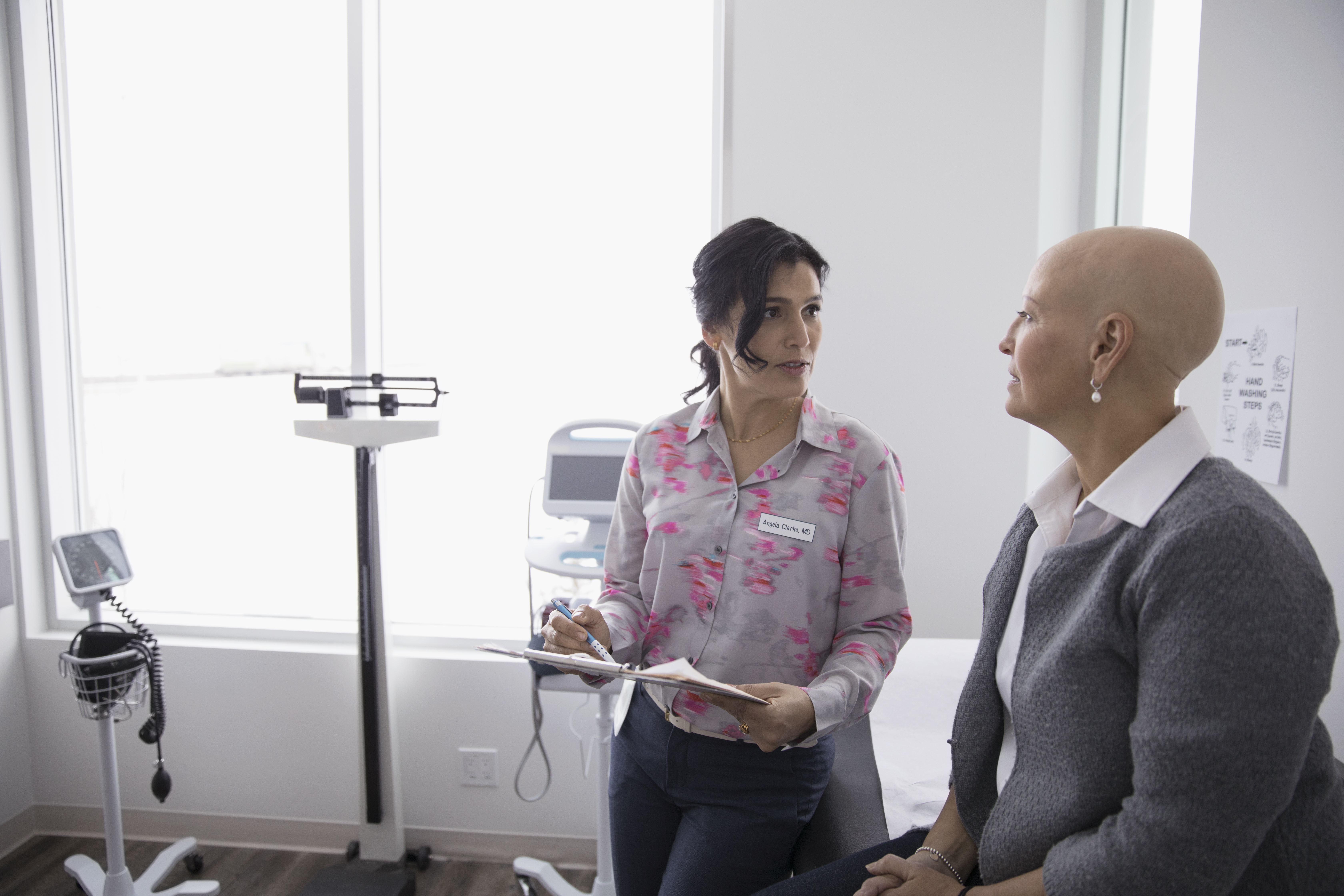 A doctor and patient talk in an examination room.