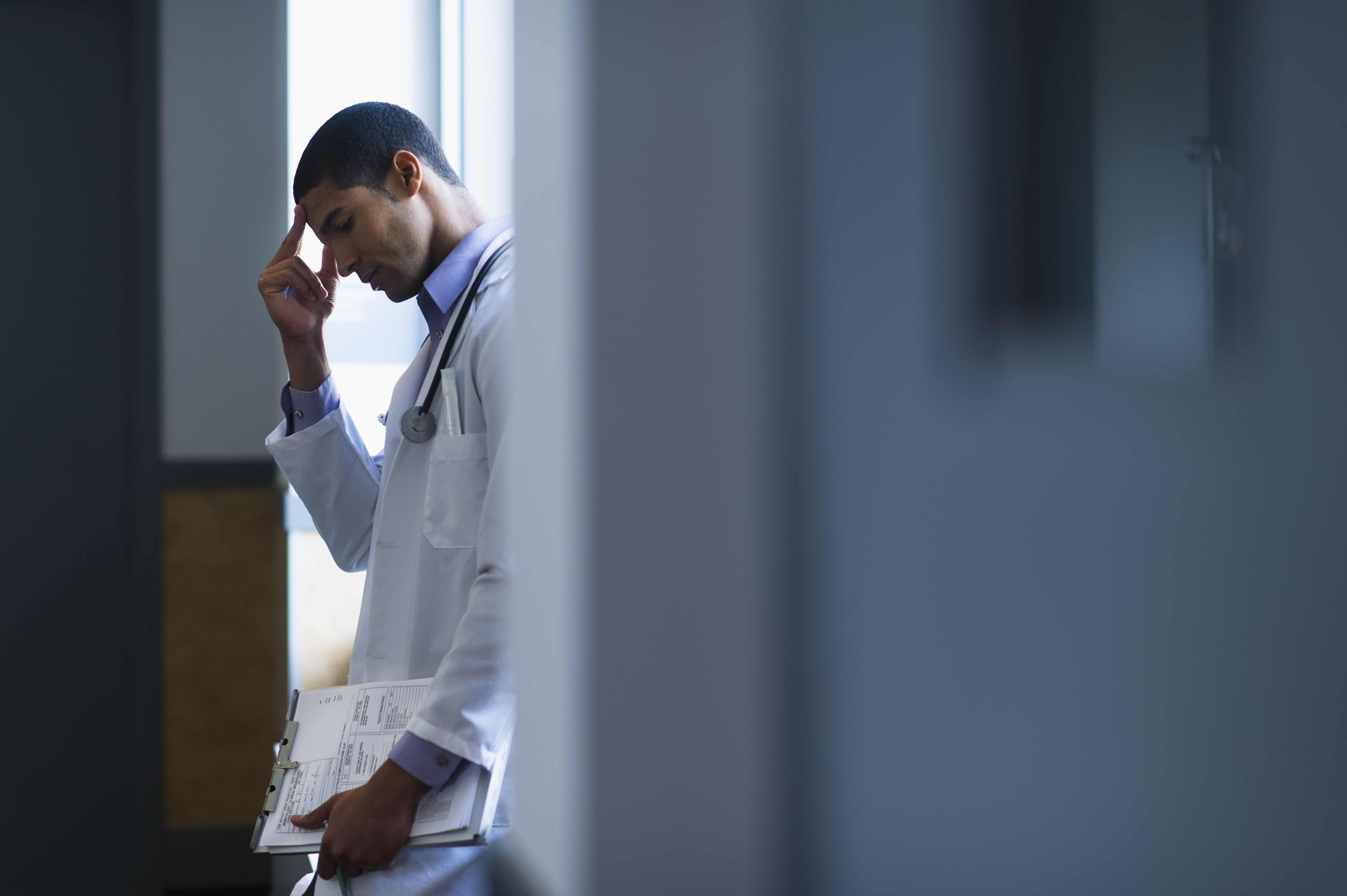 A male doctor looks down in frustration.