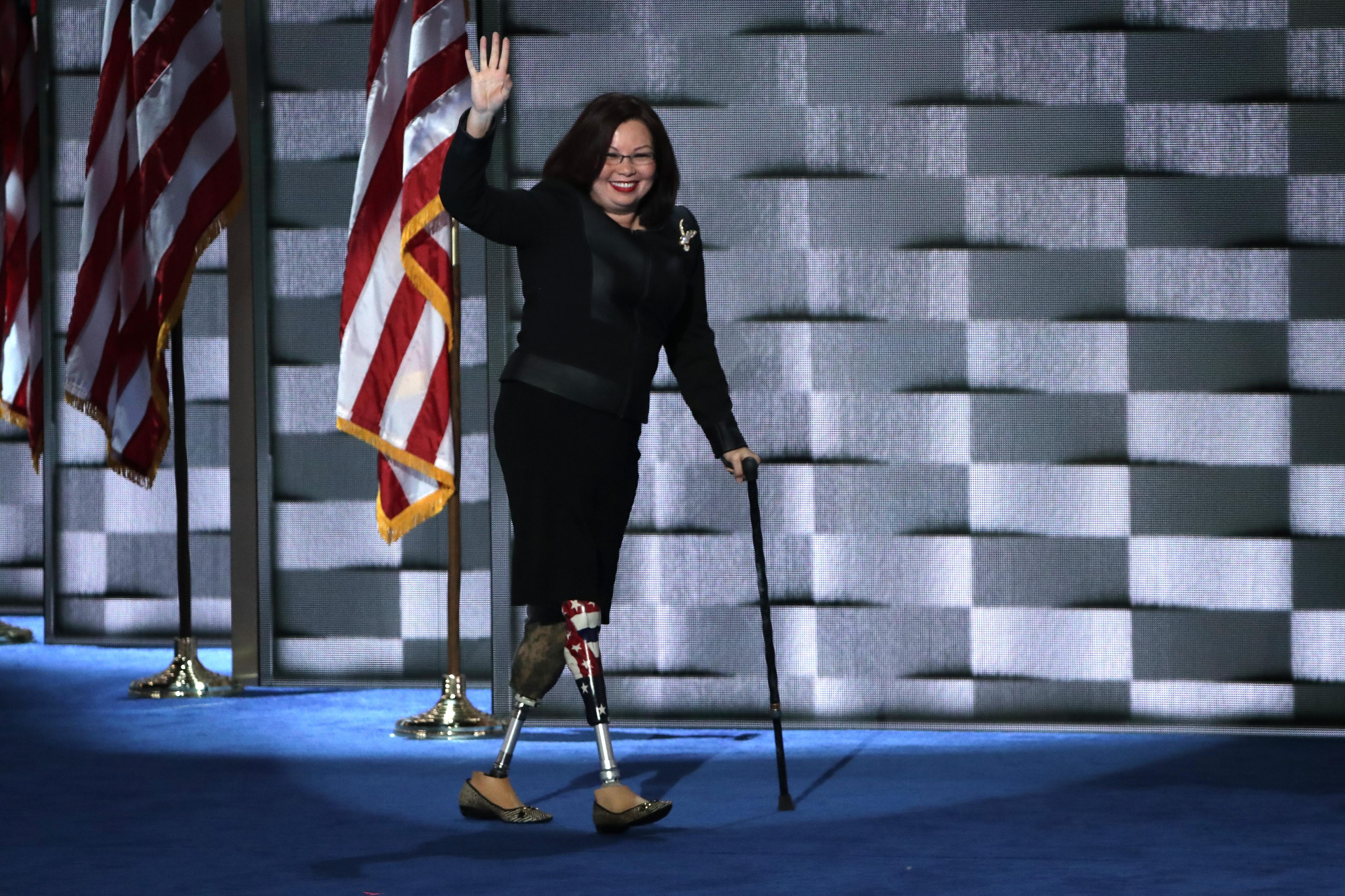 Tammy Duckworth walks across stage using prosthetic legs