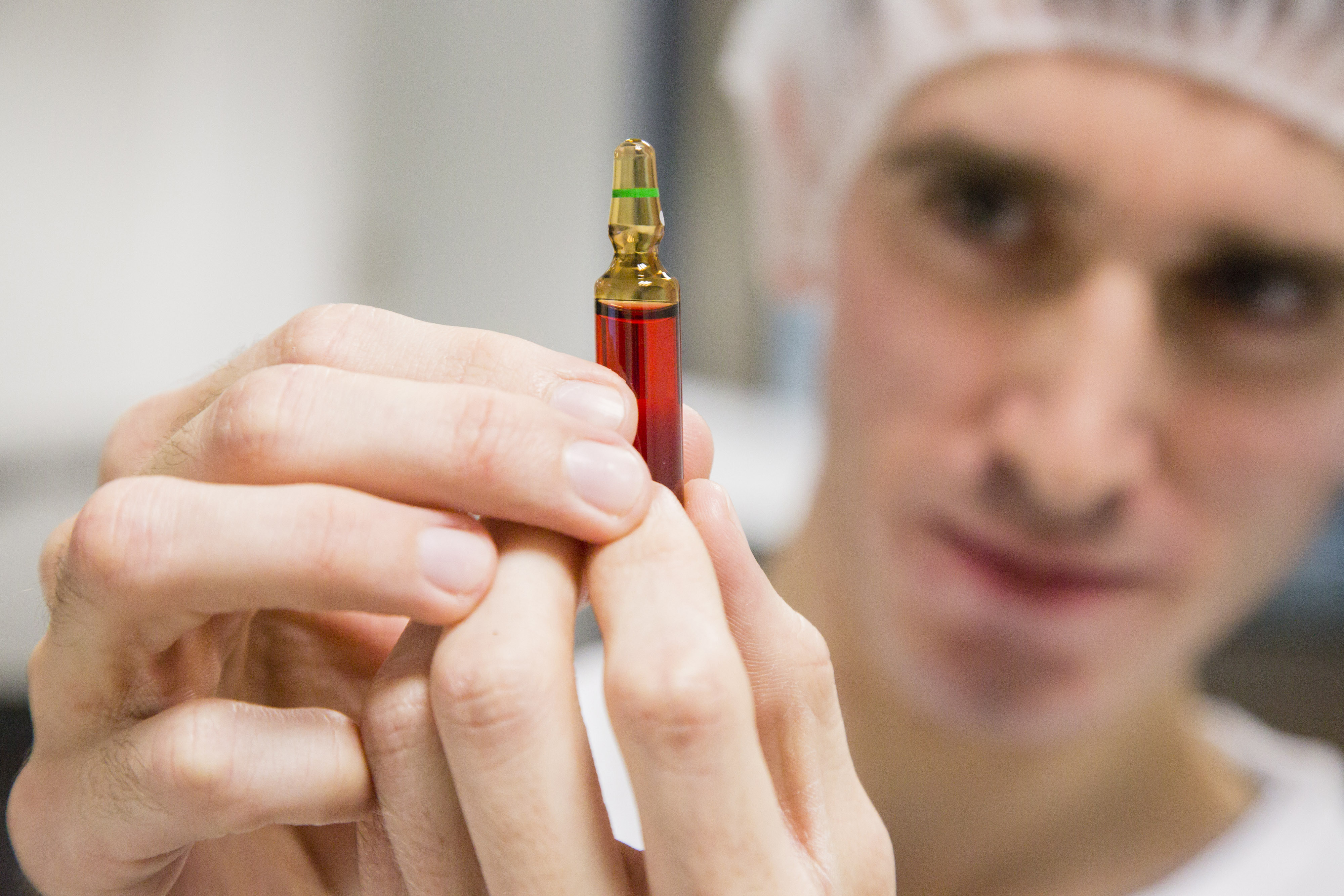 An employee inspects an ampoule of Neurobion vitamin supplement inside Merck KGaA's pharmaceutical laboratories