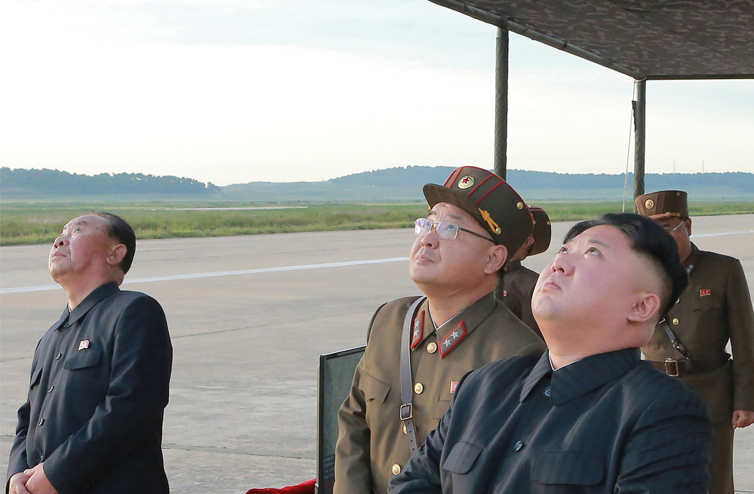 Kim Jong-un of North Korea looks up alongside military personnel in undated photo