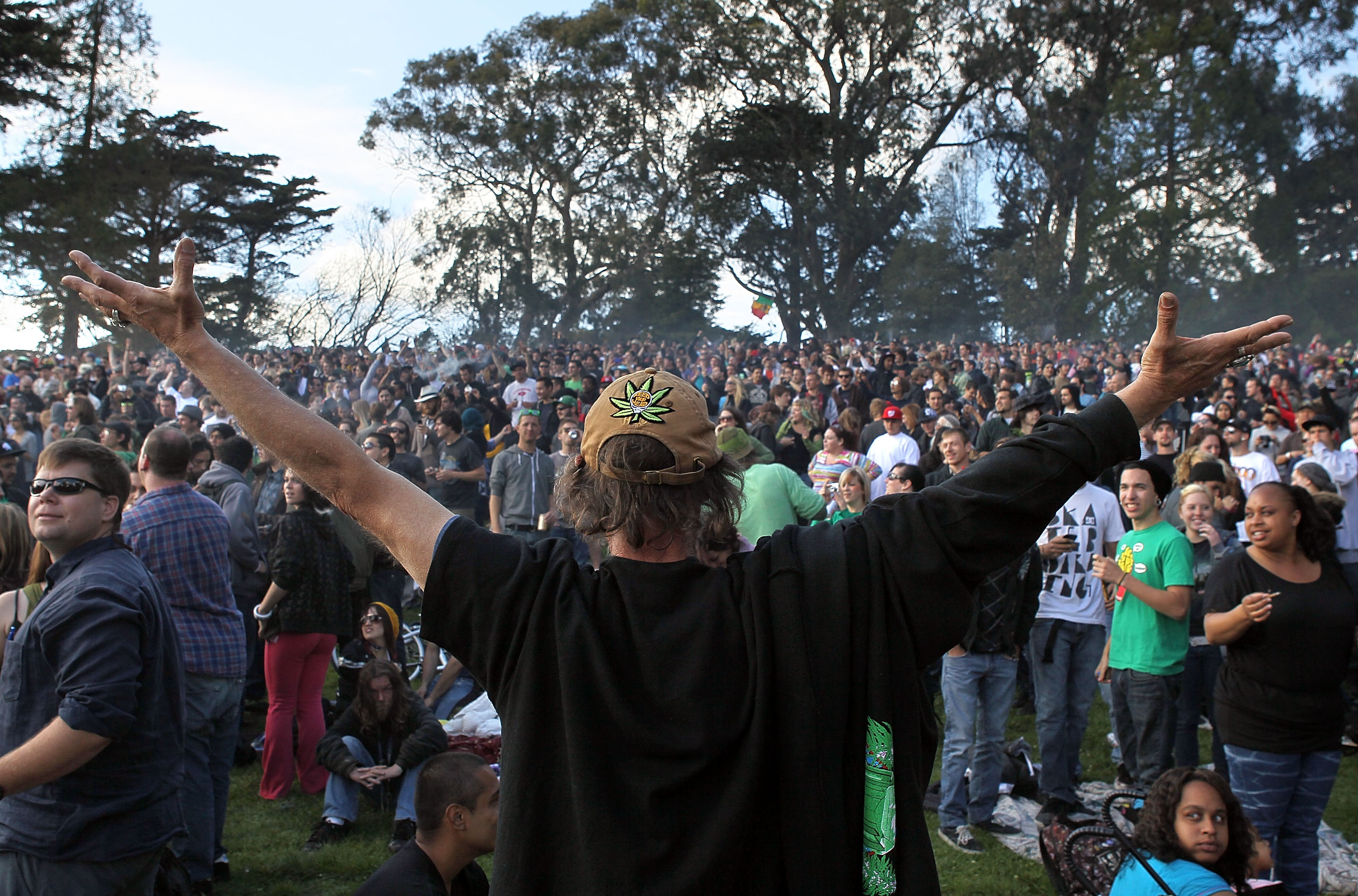 Man with arms outstretch is among pot smokers who descend on San Francisco's HIppie Hill to celebrate 4/20 Day