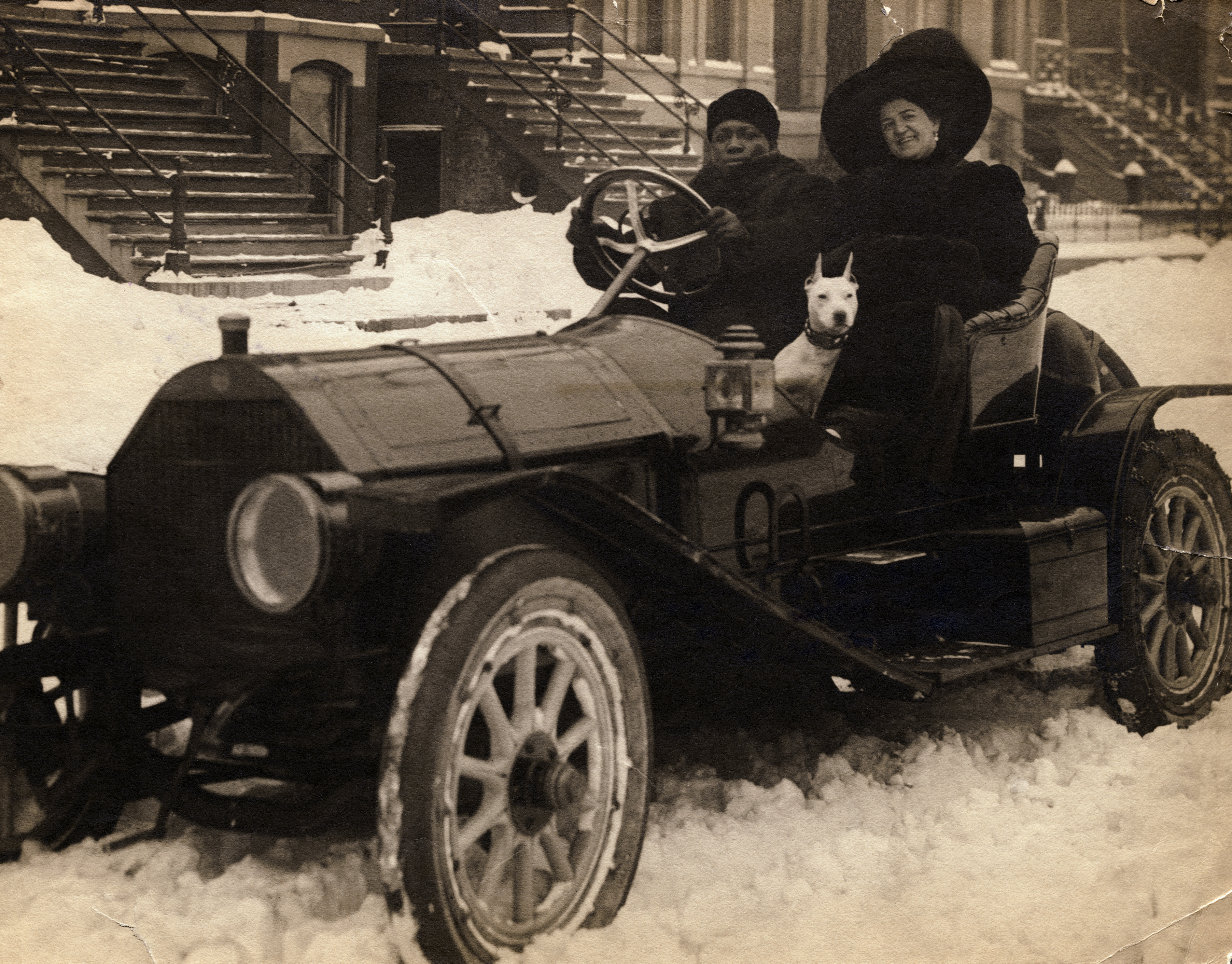 Jack Johnson sits next to his wife, who wears a large hat, in a car that is parked in the snow. They are accompanied by a dog.