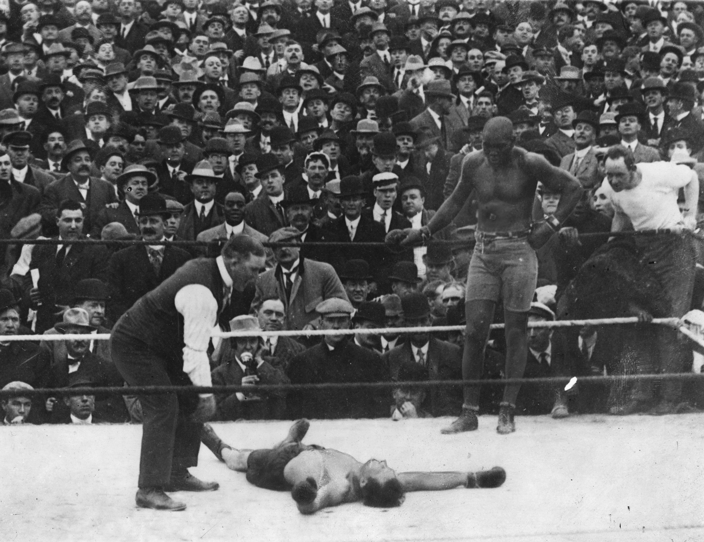 Jack Johnson leans back on the ropes while his opponent, Stan Ketchel, lays unconscious in the ring and the referee bends over him to count him out.