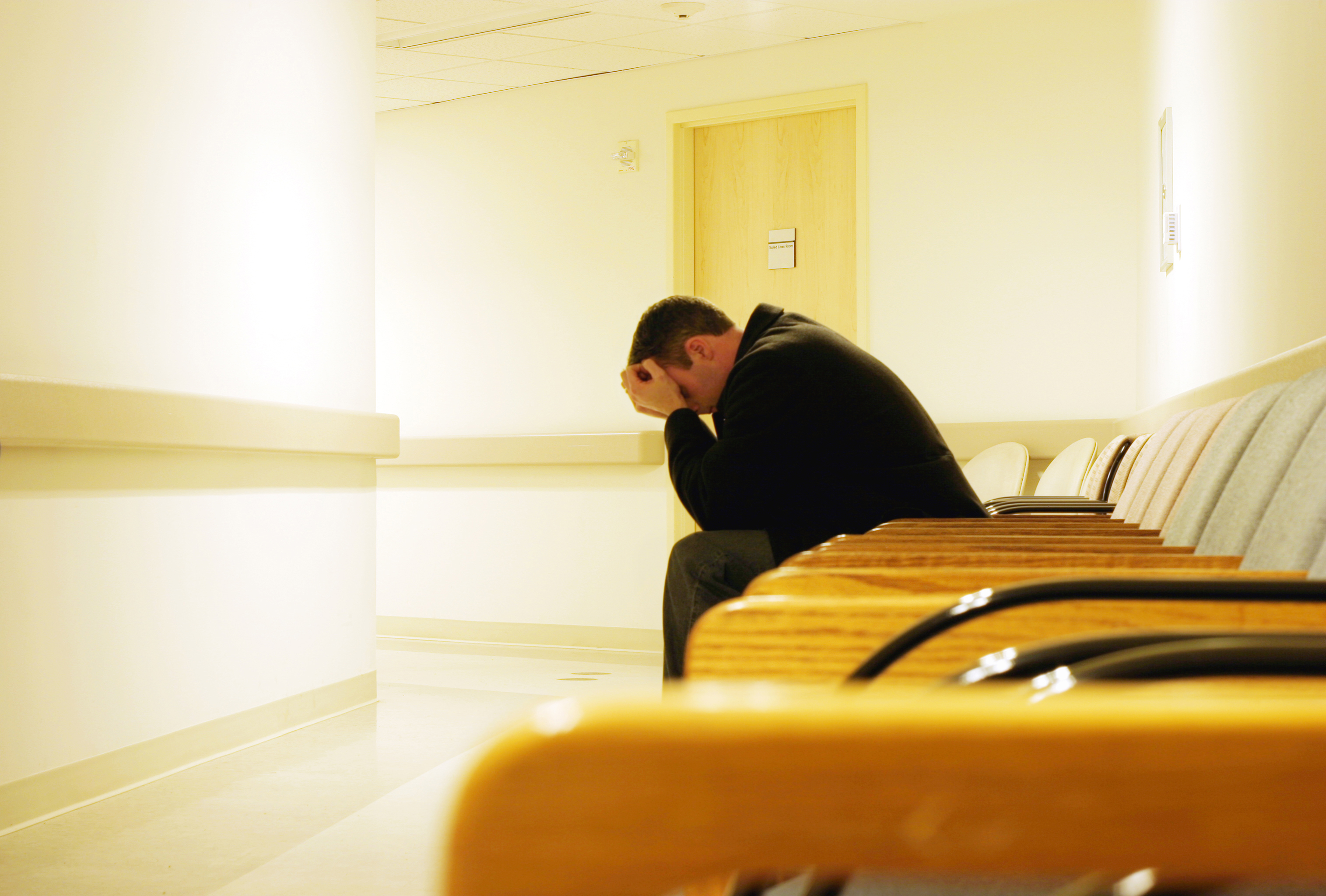 Man sits in doctor's office waiting room with his heads in his hands.