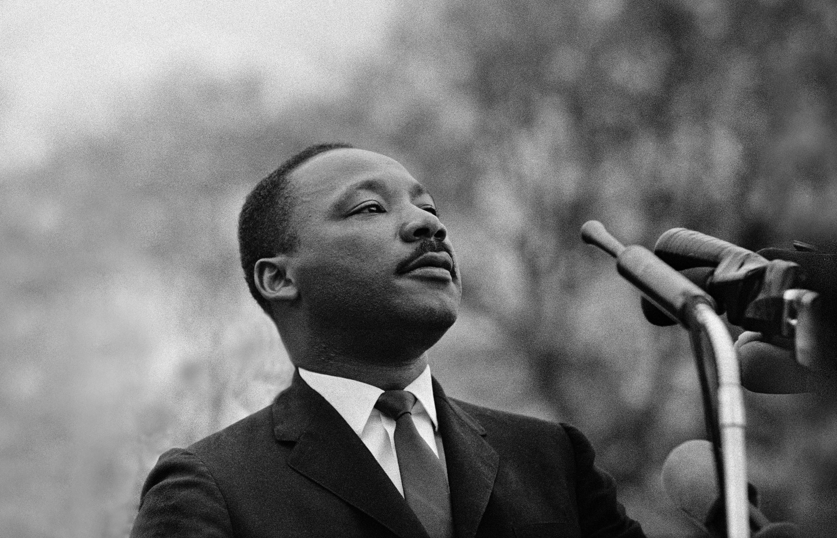 Dr. Martin Luther King, Jr. stands in front of several microphones and looks over a crowd of 25,000 out of frame in front of him