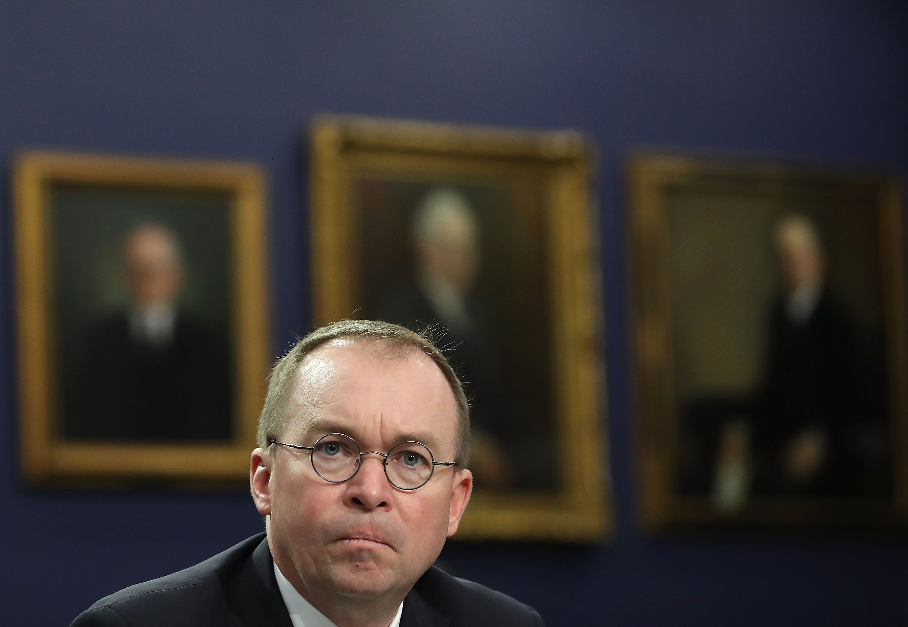 CFPB and Office of Management and Budget director Mick Mulvaney stares at the camera with a frown on his face. he wears glasses and sits in front of three large portraits which are out of focus.