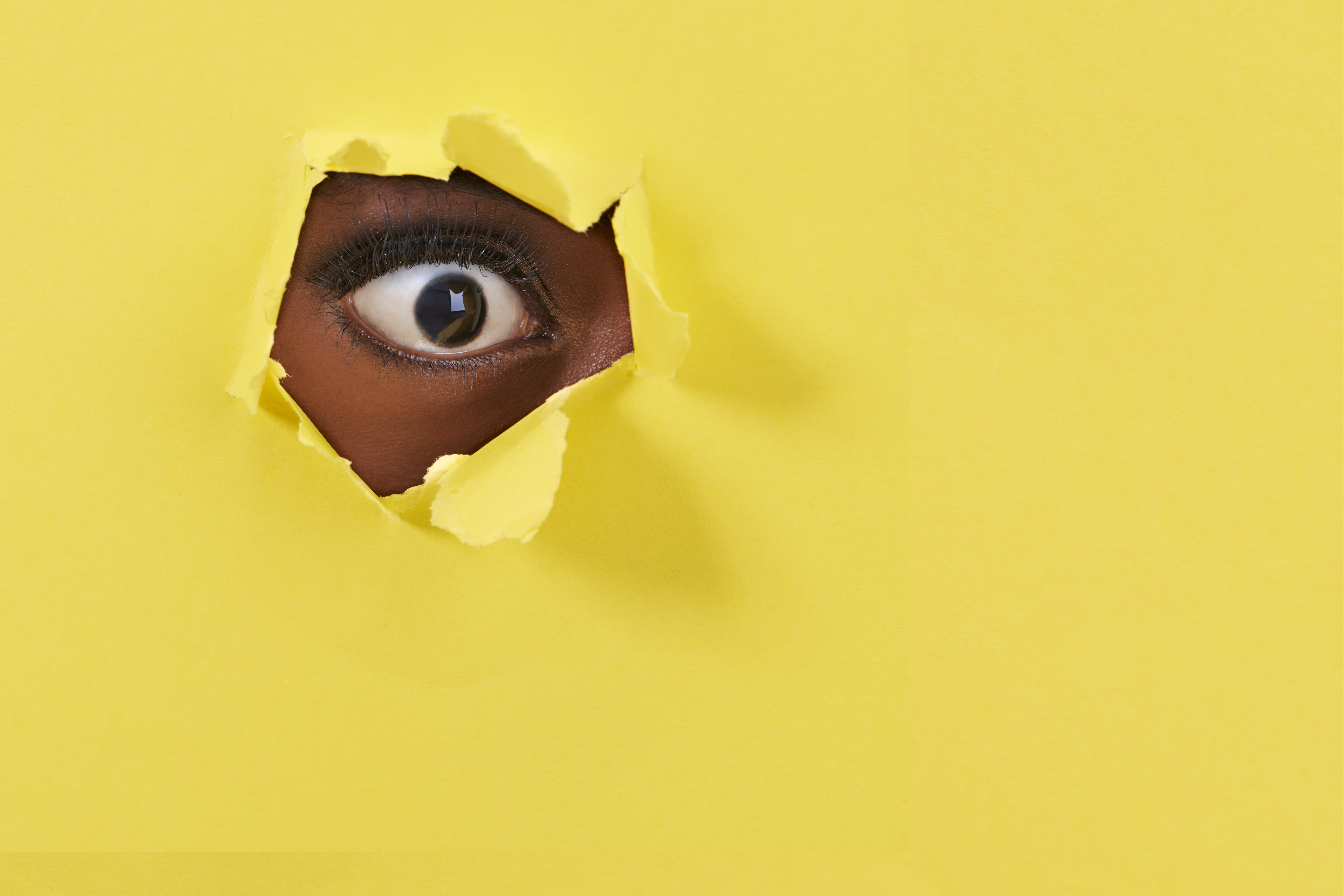 A view of a woman's eye looking through a hole in yellow paper