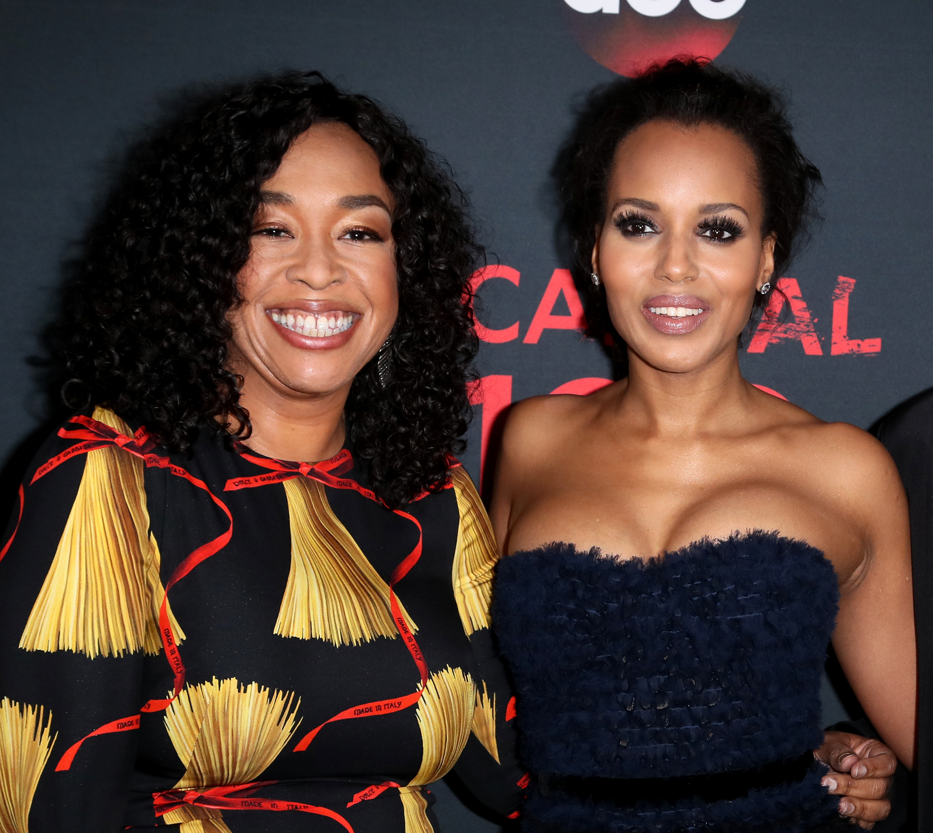 Shonda Rhimes and Kerry Washington pose together, smiling, on the red carpet for Scandal's 100th episode