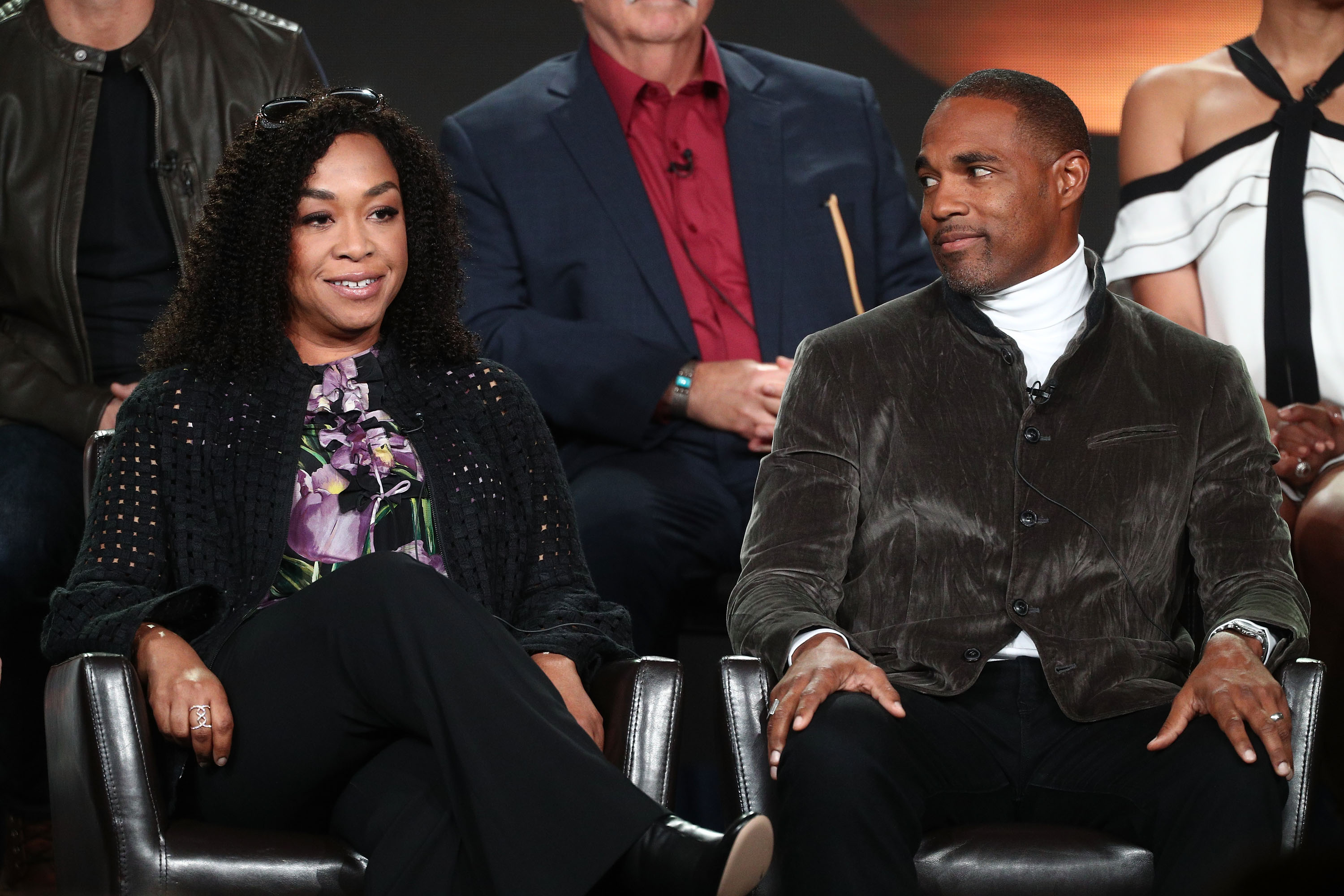 Shonda Rhimes sits in a chair speaking on stage, actor Jason George sits on her left and looks enthralled by what she is saying.