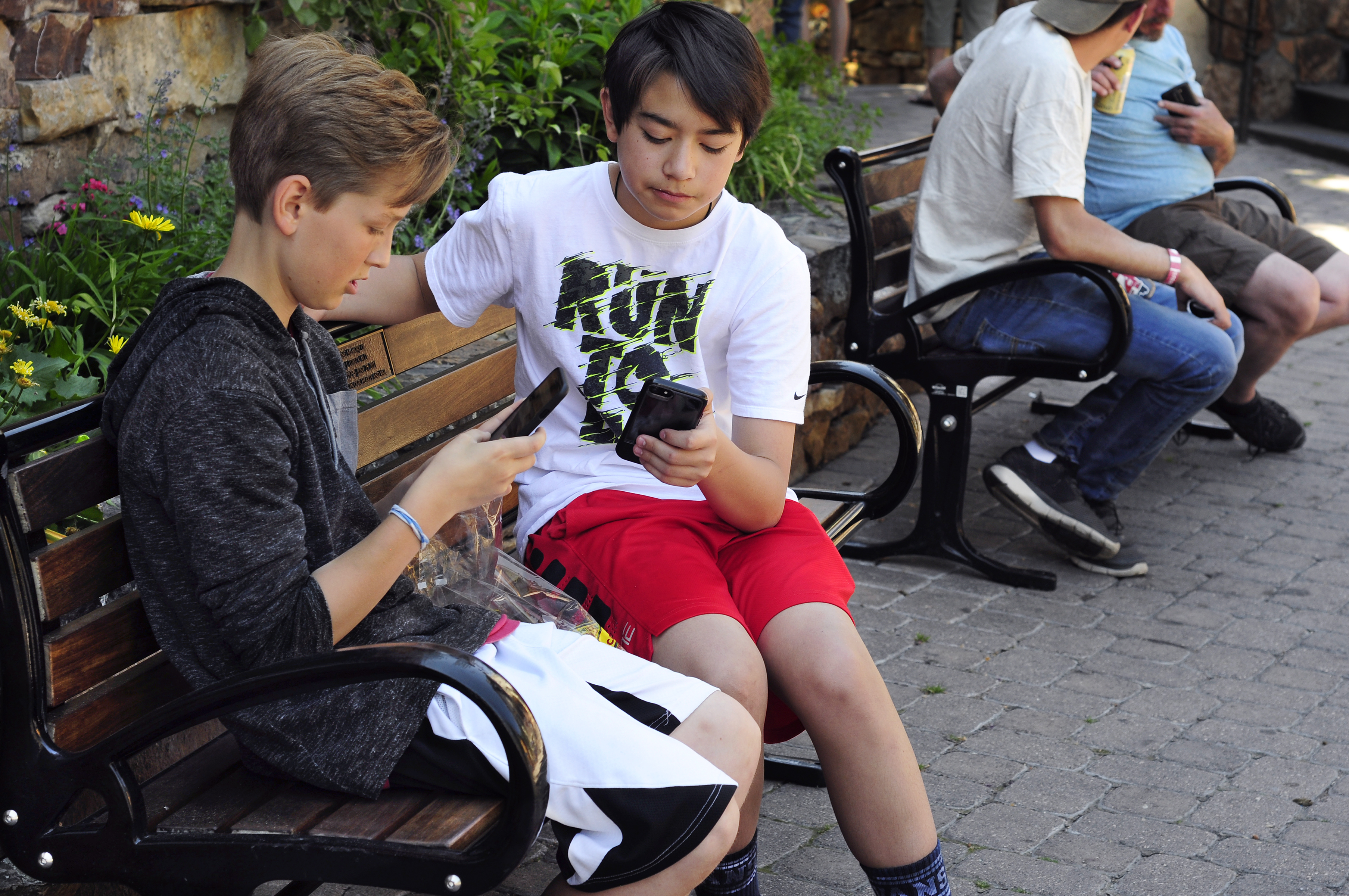 Two teenage boys use their smartphones as they sit on a bench in Vail, Colorado.