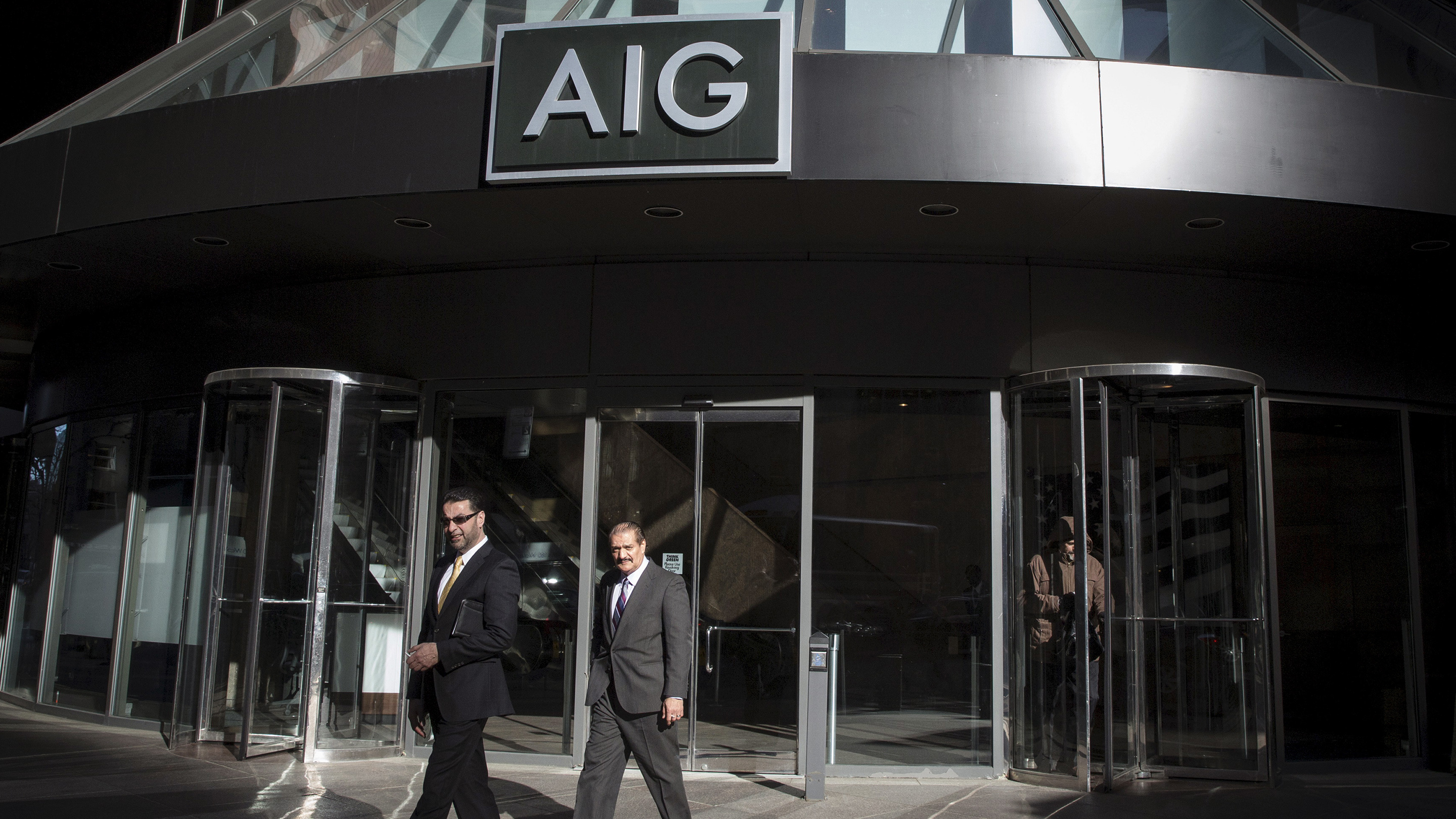 People exit the AIG building in New York's financial district