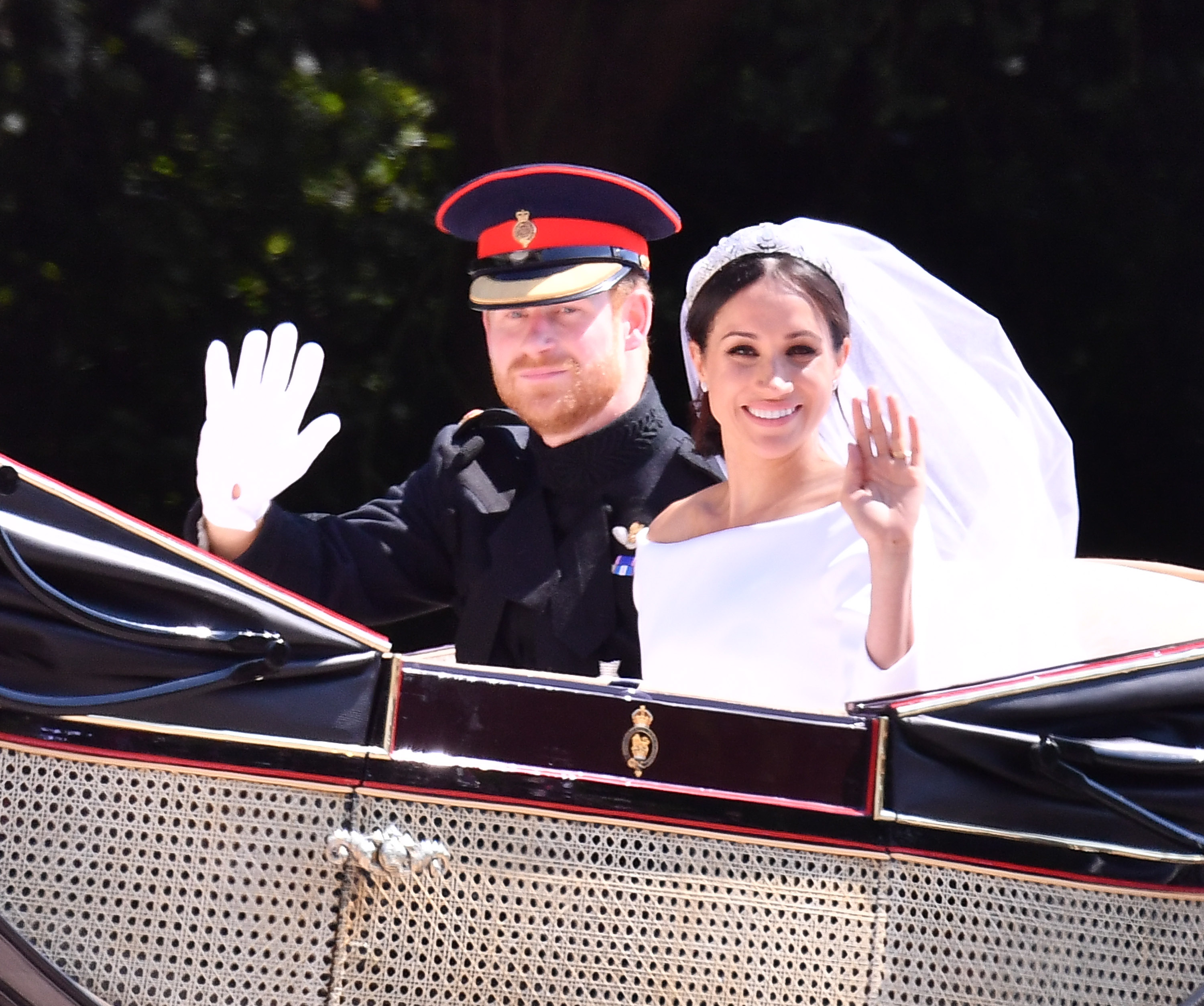 Prince Harry and Meghan Markle wave on carriage ride around Windsor after their wedding.