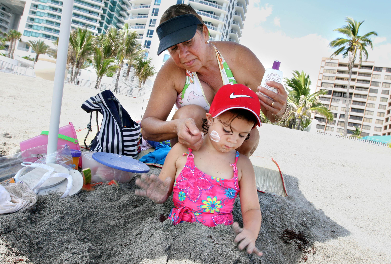 Vera Casanova, rear, applies sunscreen on her daughter Julie