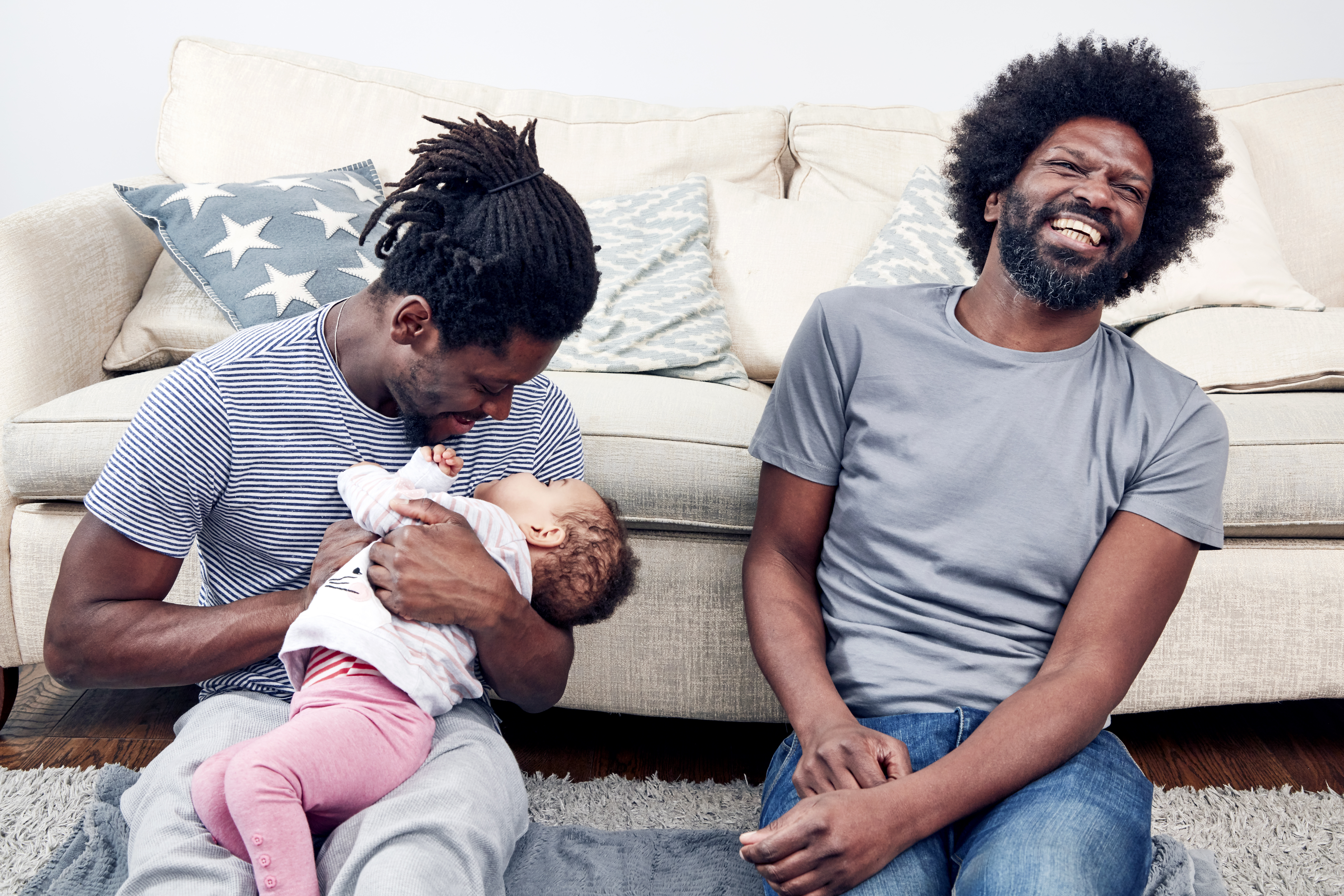 Two black fathers are beaming as they sit on the floor and play with their daughter