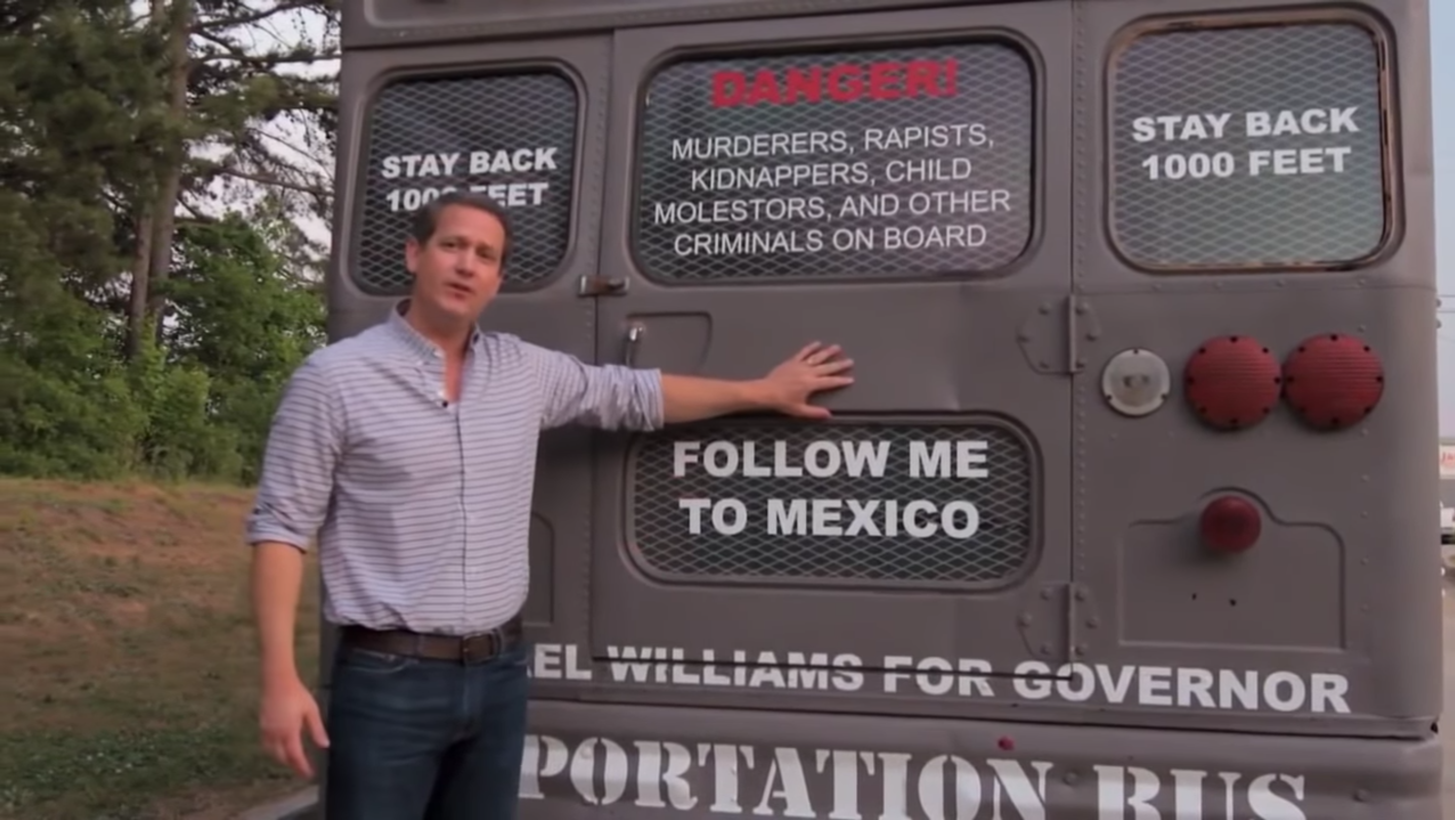 """Georgia state Sen. Michael Williams stands in front of a gray bus and places his hand on the back door over the words """"FOLLOW ME TO MEXICO"""""""