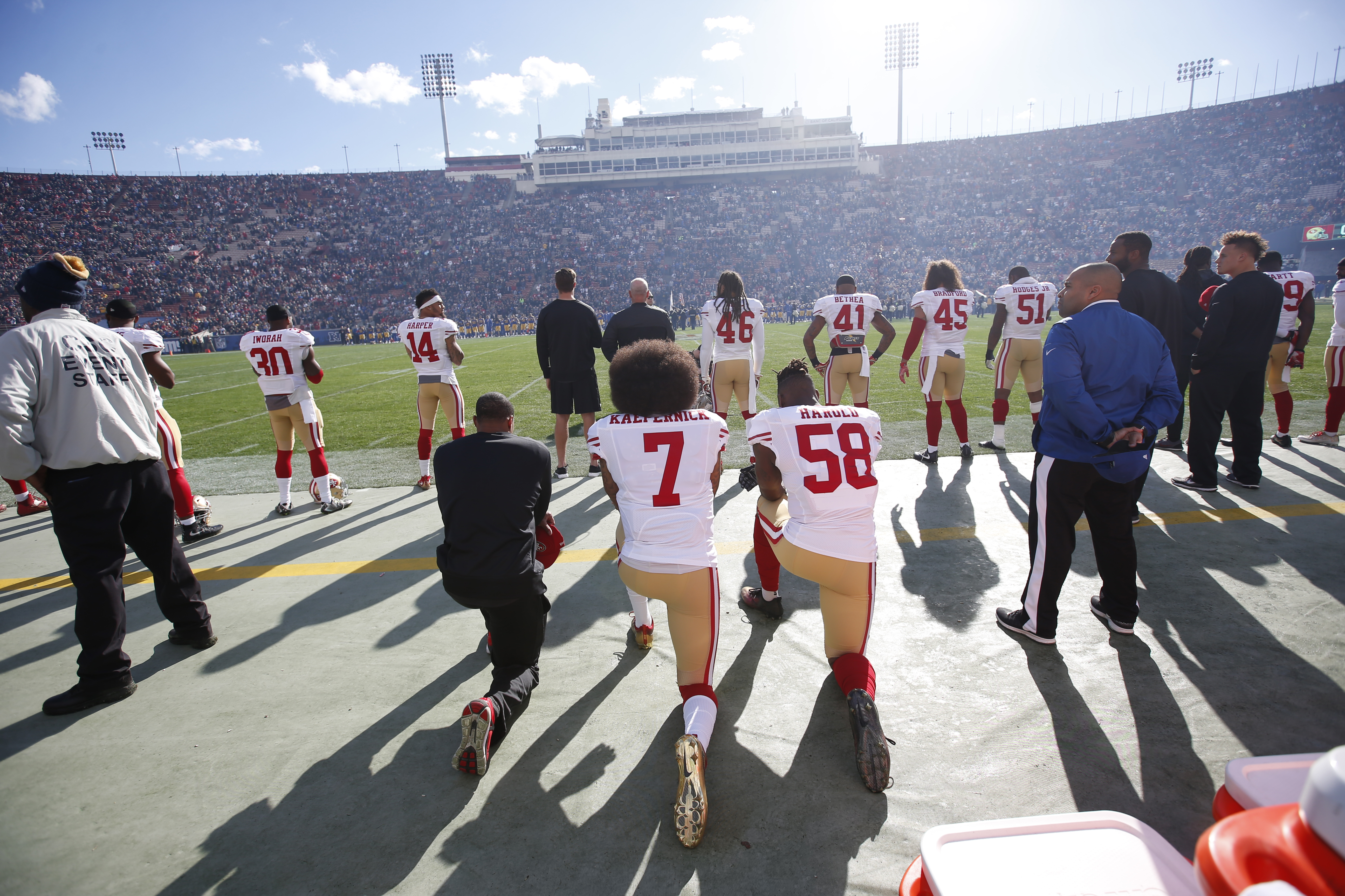 Eric Reid #35, Colin Kaepernick #7 and Eli Harold #58 of the San Francisco 49ers kneel next to each other on the sideline, during the anthem, prior to the game against the Los Angeles Rams at the Los Angeles Coliseum.