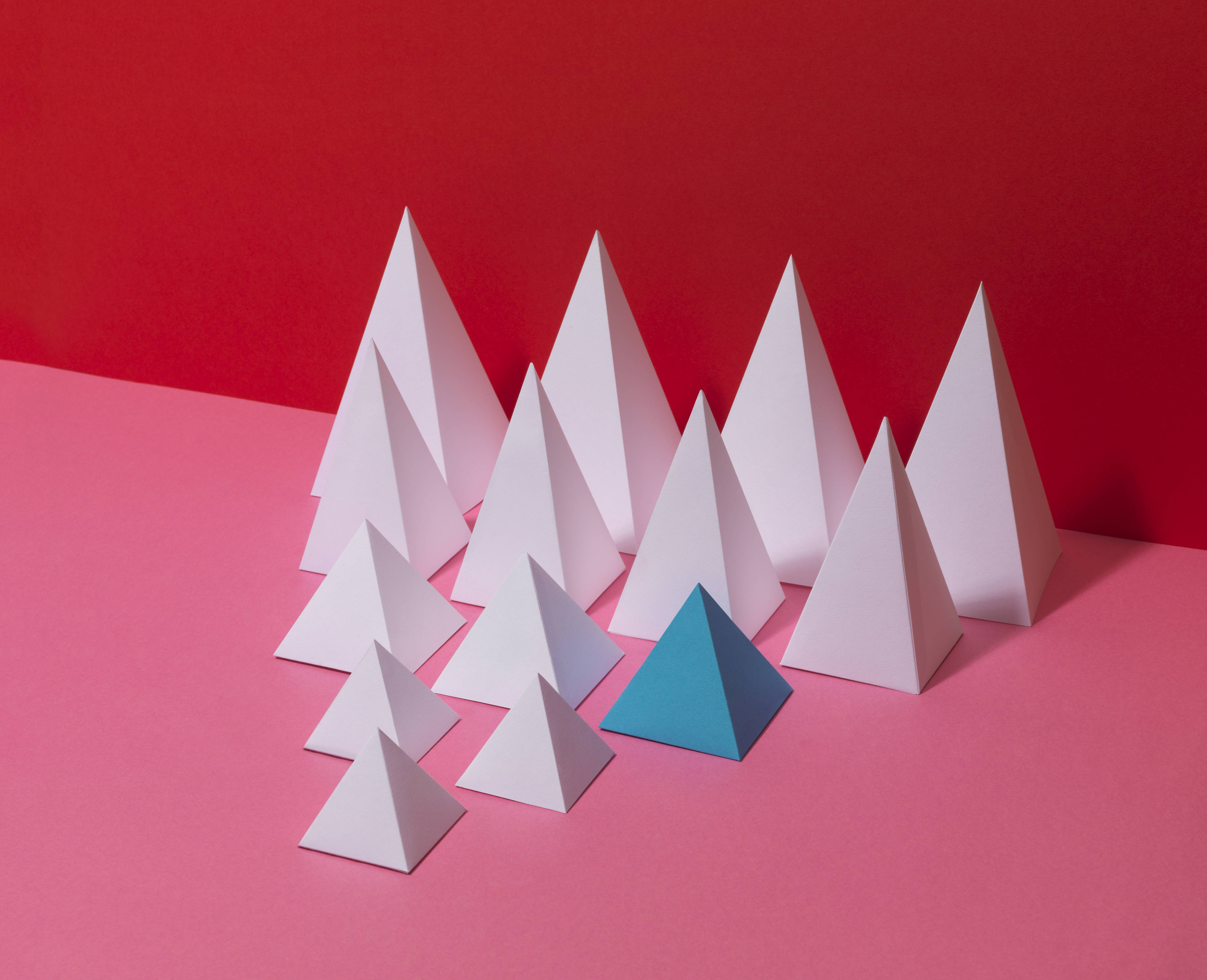 Group of white pyramids, one blue pyramid, on red background