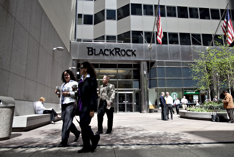 Pedestrians walk outside the headquarters of BlackRock Inc.