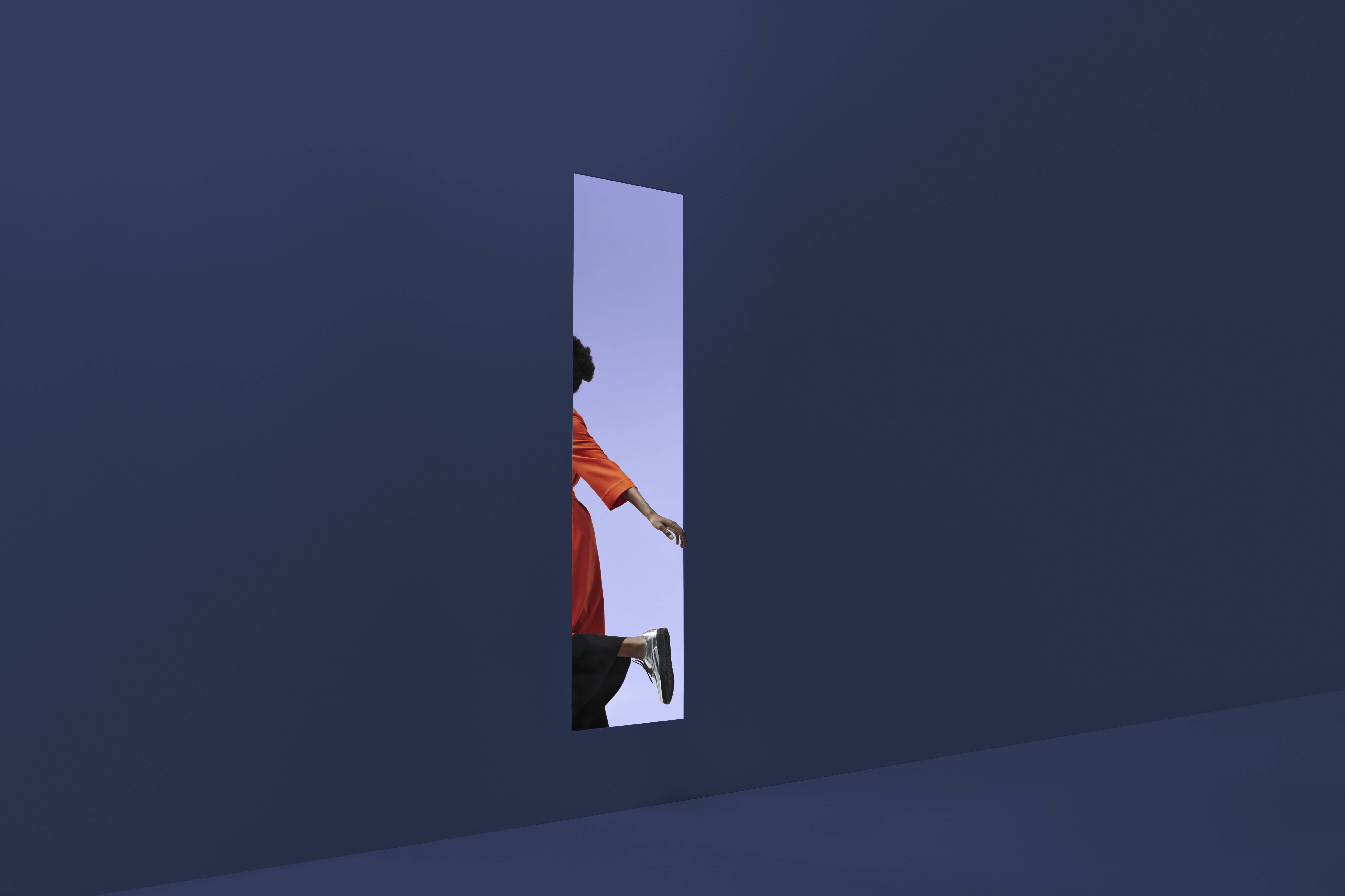 woman's arm and leg are visible as she passes through a doorway