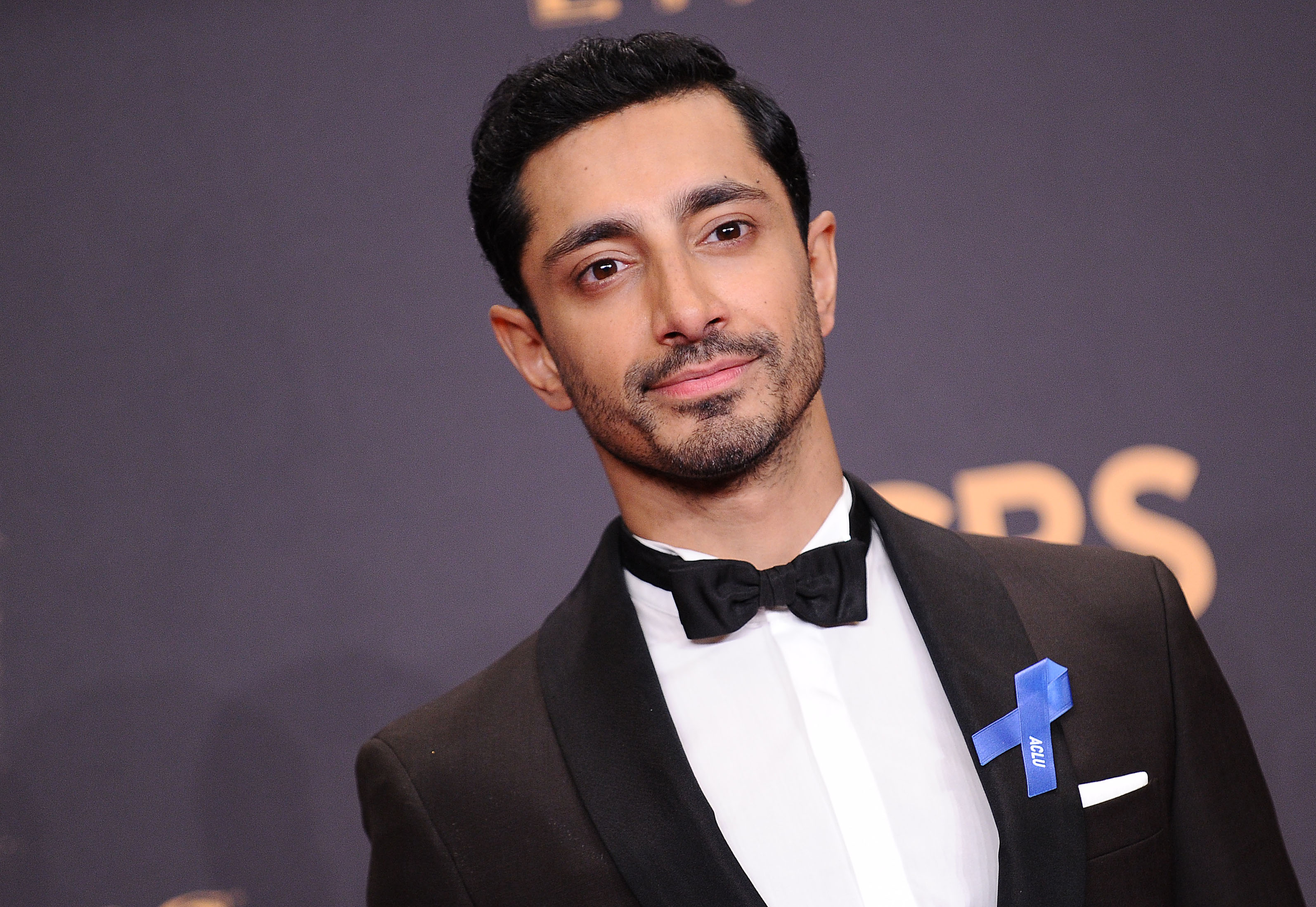 Riz Ahmed poses at the Emmy Awards. he wears a bowtie and a blue ribbon.