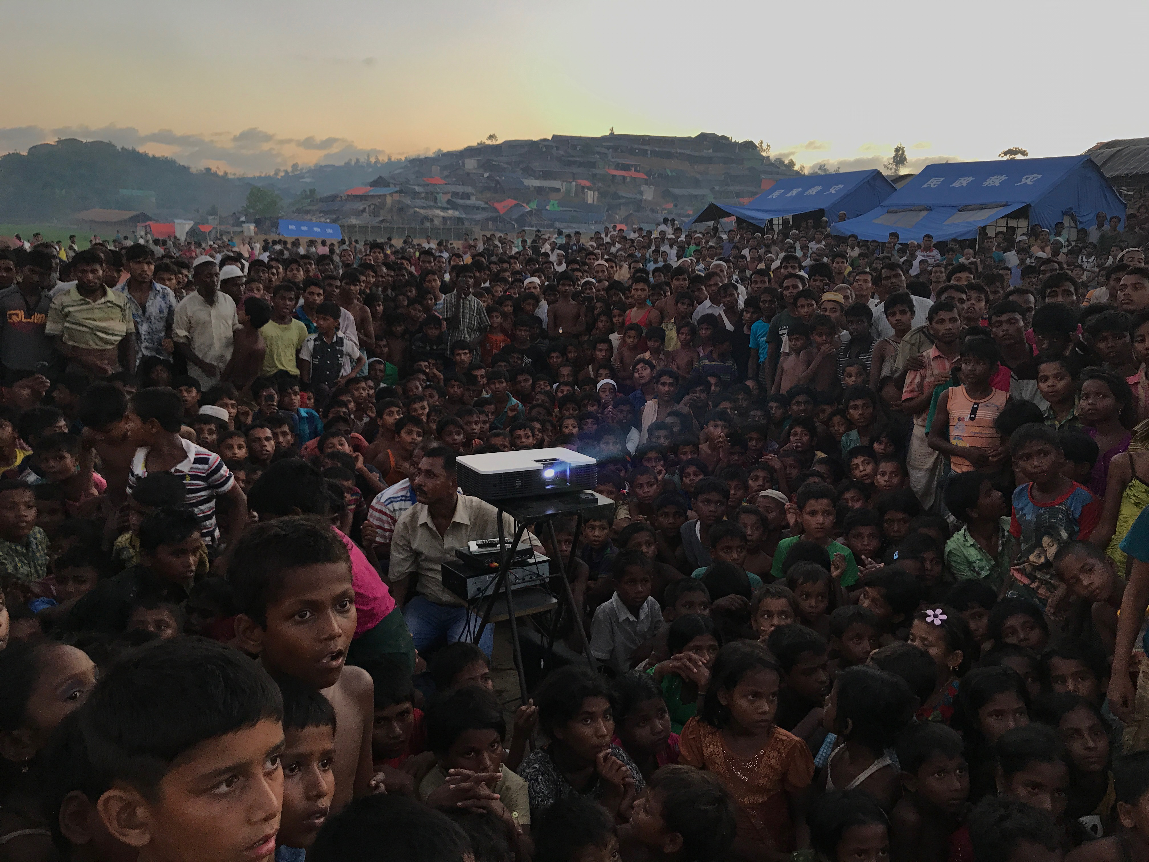 "Photographer of the Year Grand Prize, ""Displaced."" Rohingya children watching an awareness film about health and sanitation near Tangkhali refugee camp in Ukhiya. Shot on iPhone 7."
