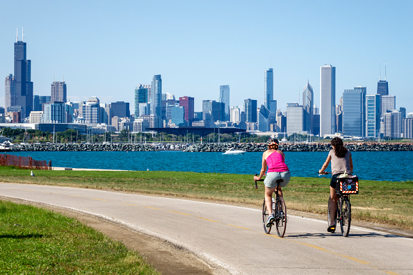 Illinois, Chicago, South Side, Lake Michigan, 39th Street Beach, Lakefront Trail, woman, friends, biker, bicycle, riding, city skyline, high rise skyscraper buildings,
