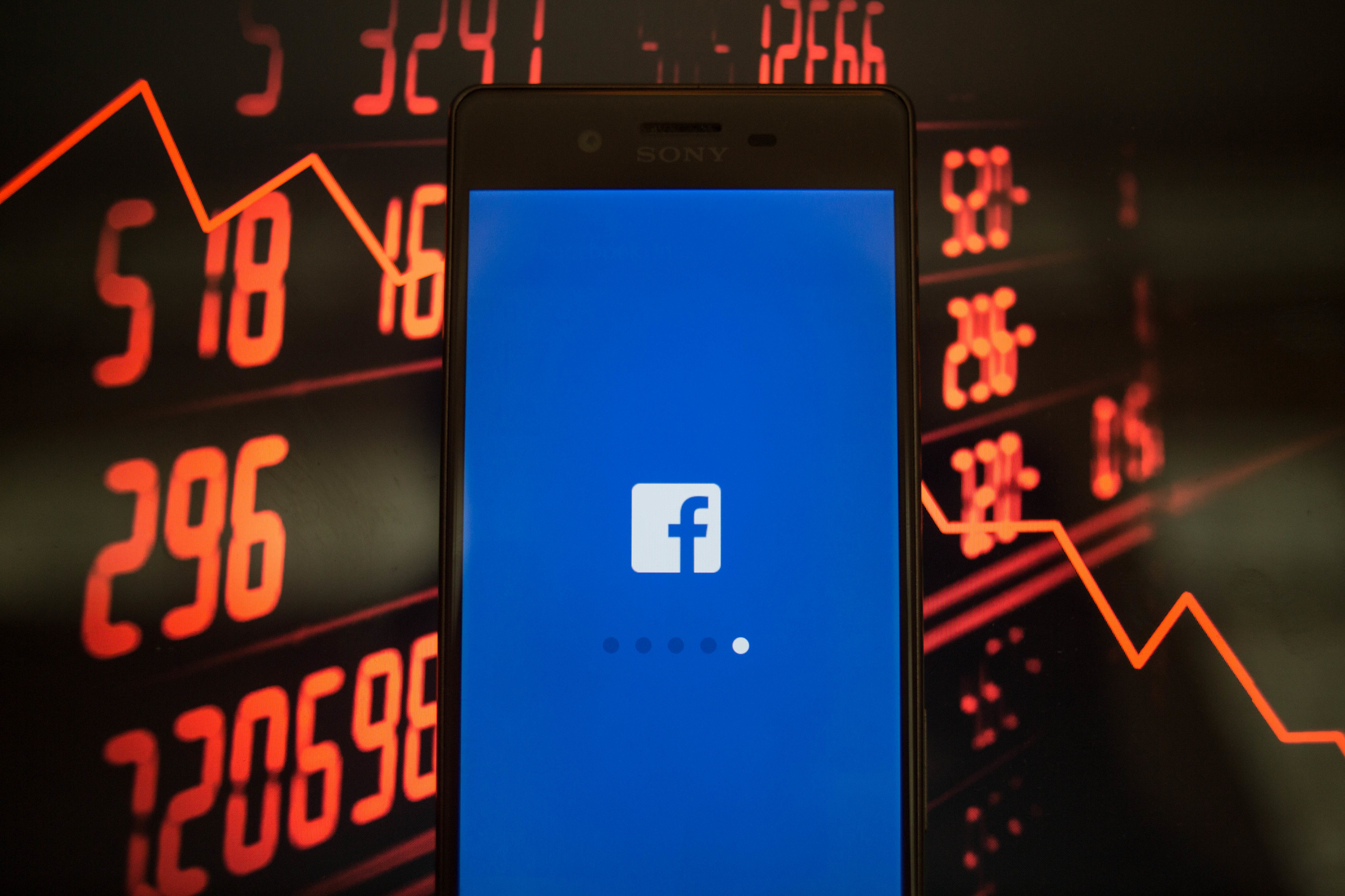 A smartphone displays the Facebook application with a