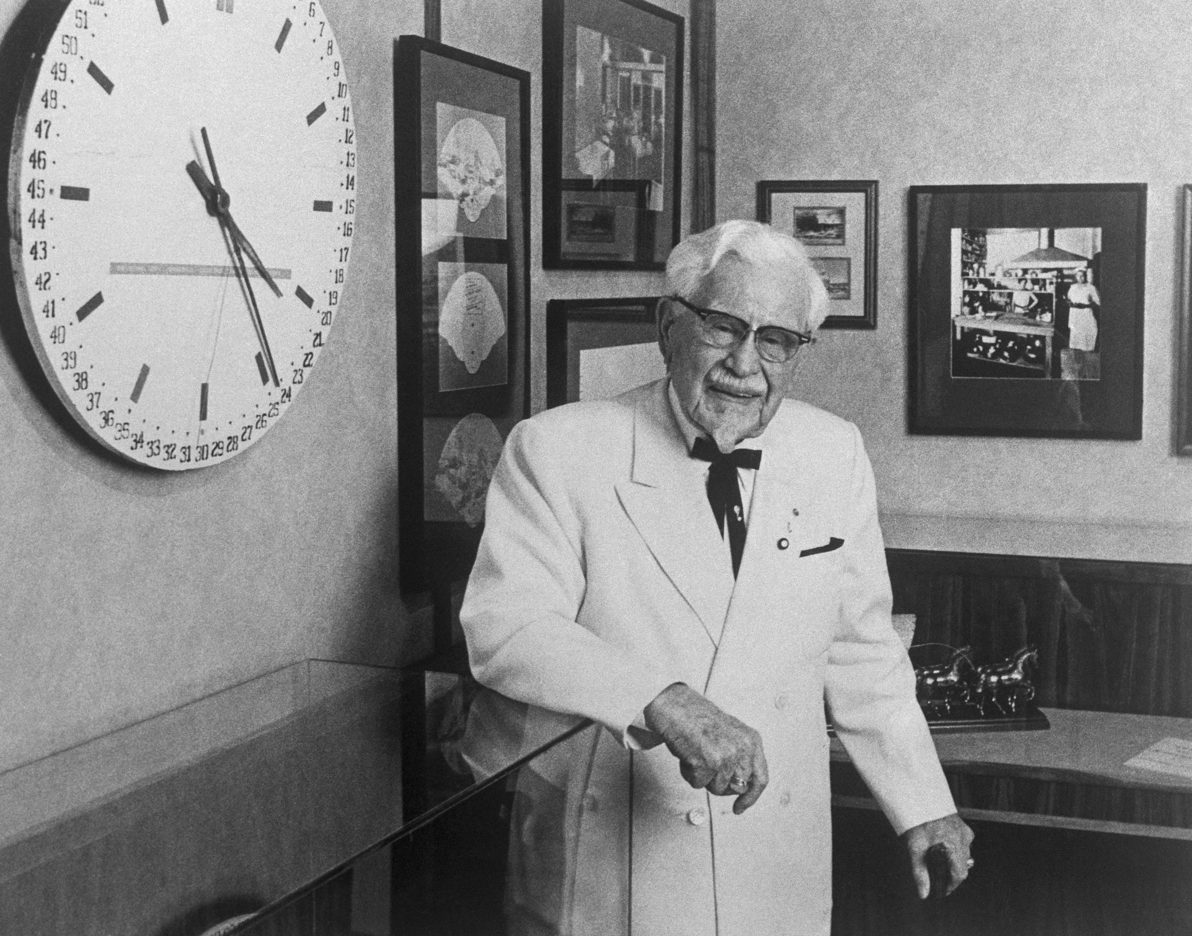 Colonel Harland Sanders Standing by Wall Clock