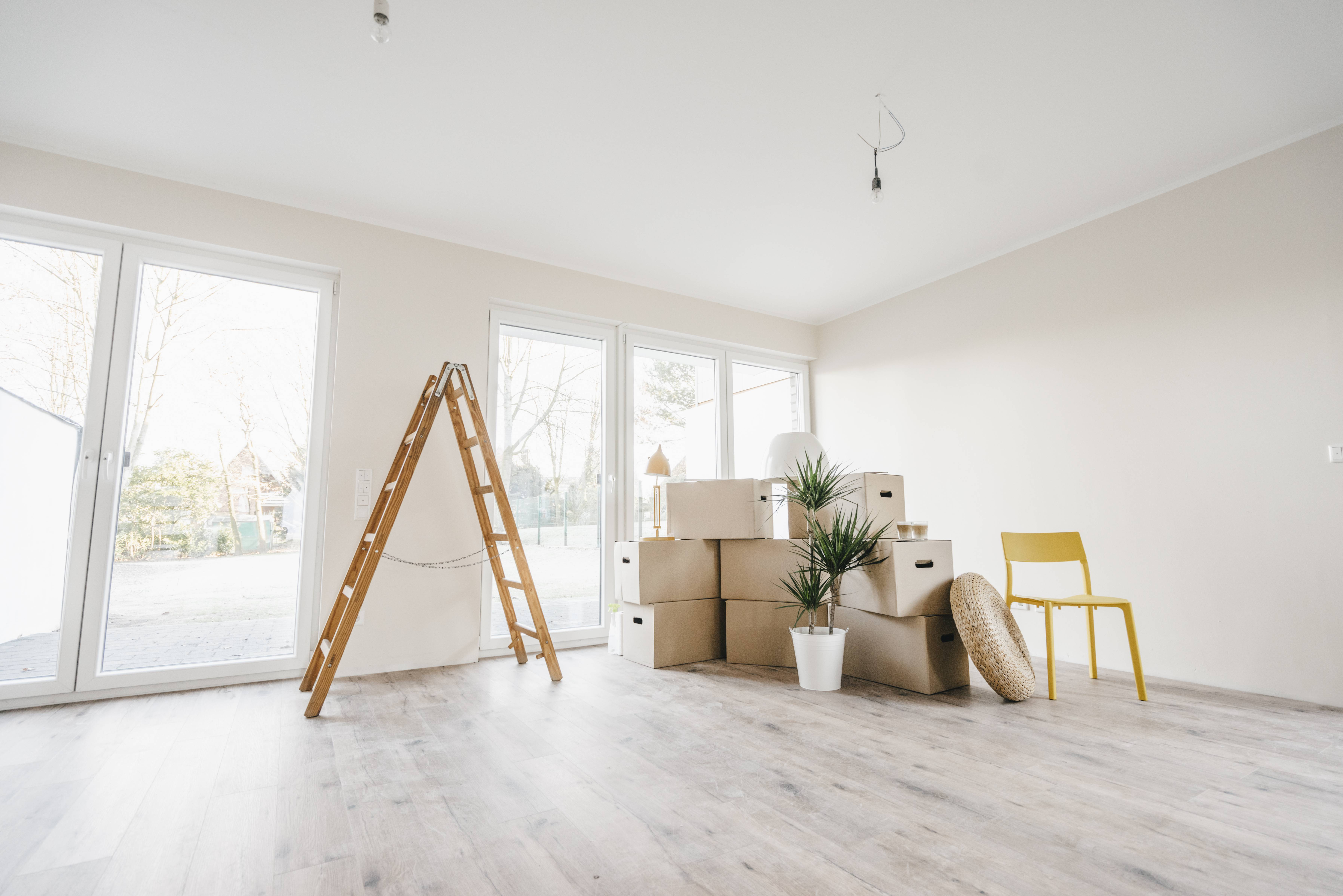 Moving boxes and ladder in empty room of a new home