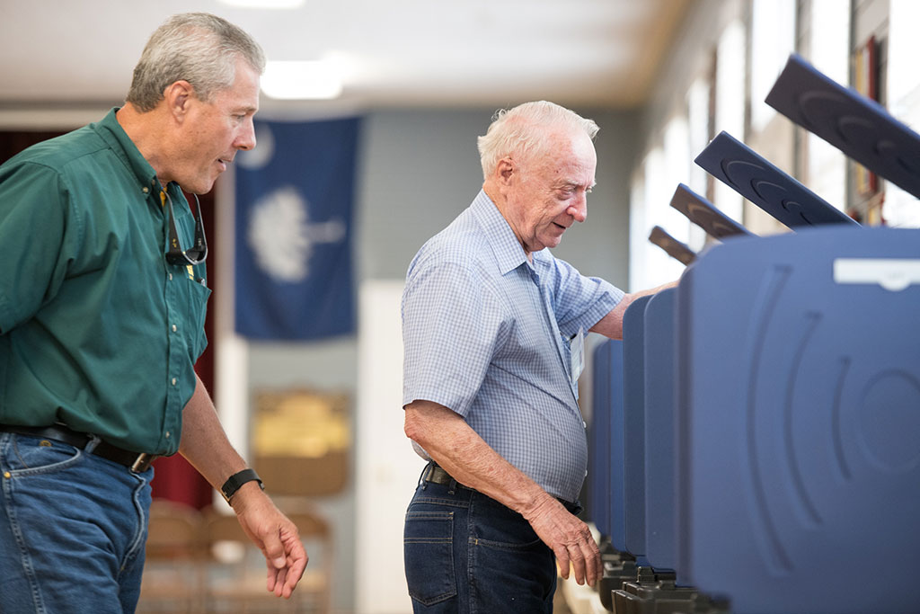 An older man stands at a voting booth while another man watches.