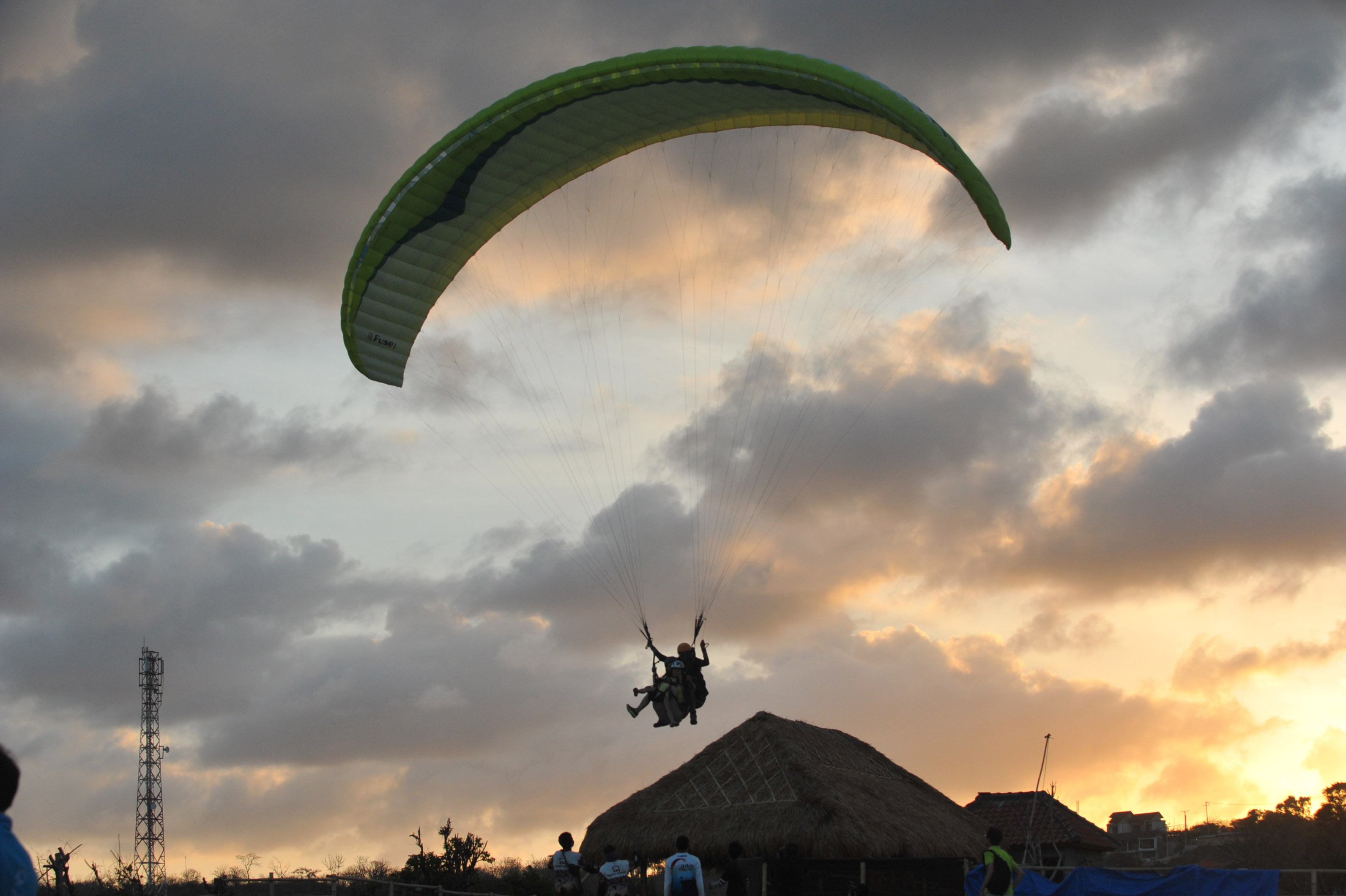 Tourists fly joint paragliding in Nusa Dua