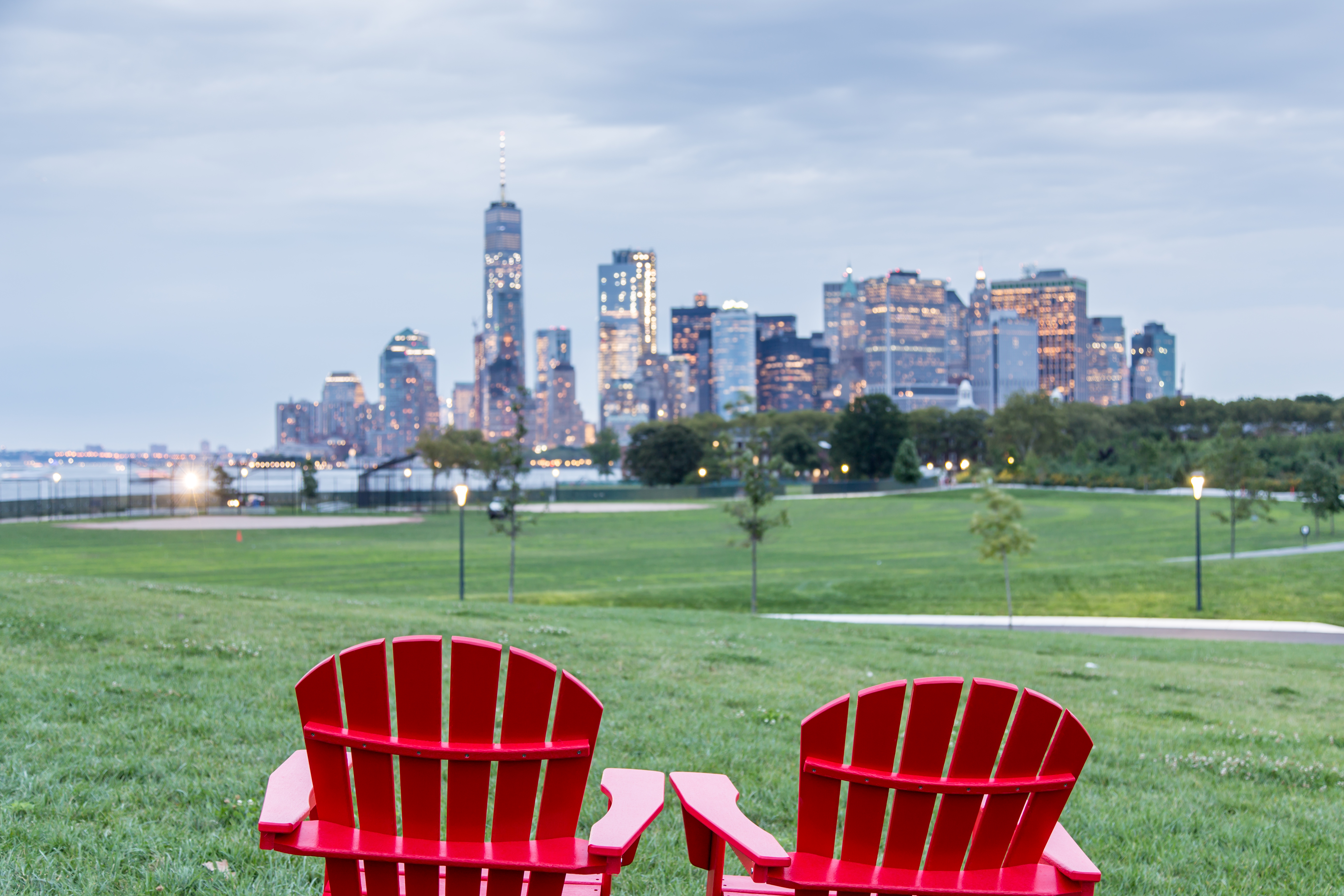 Red Adirondack chairs with a view of Downtown Manhattan