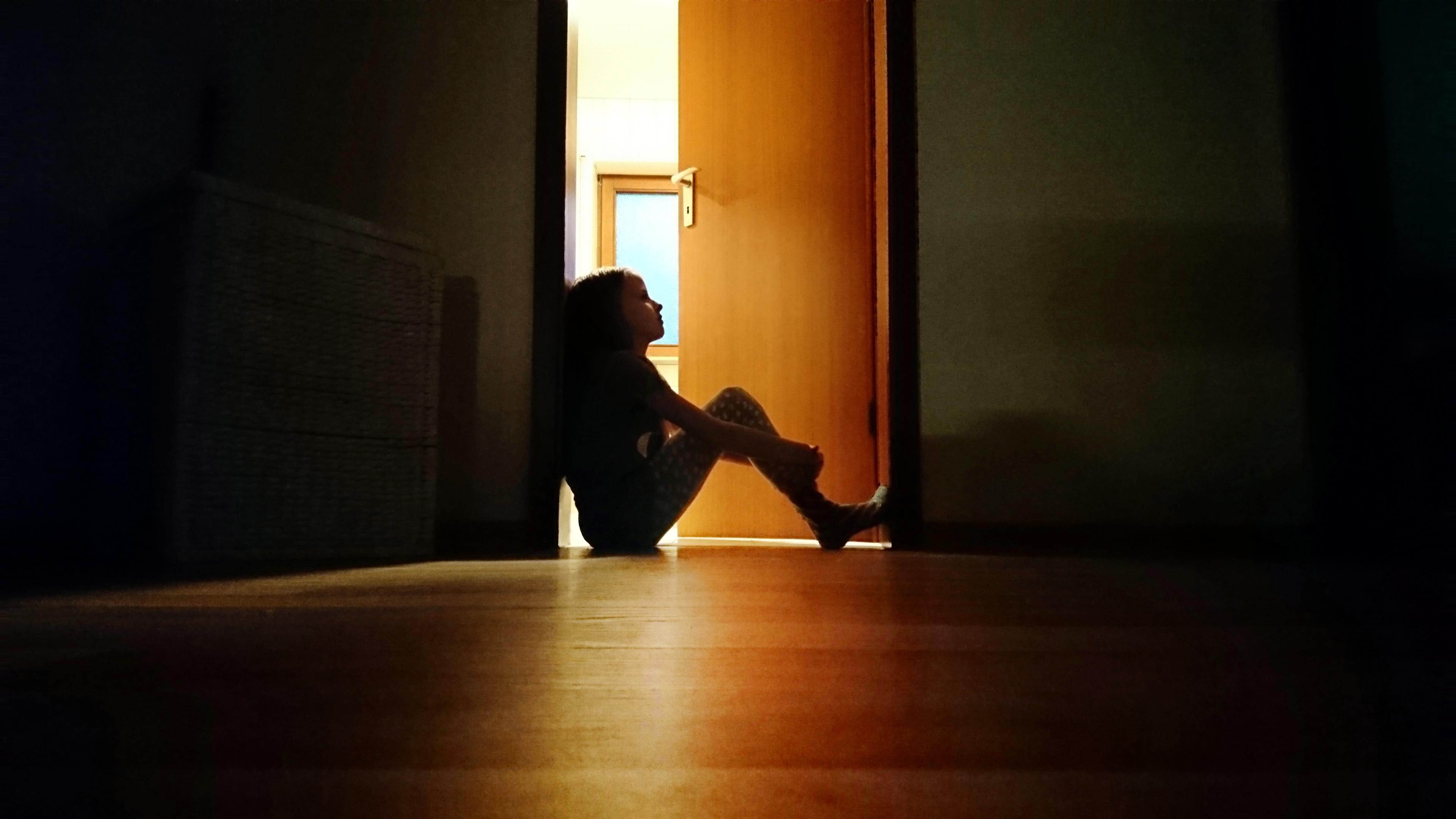 Backlit child sitting in a dark doorway in contemplation