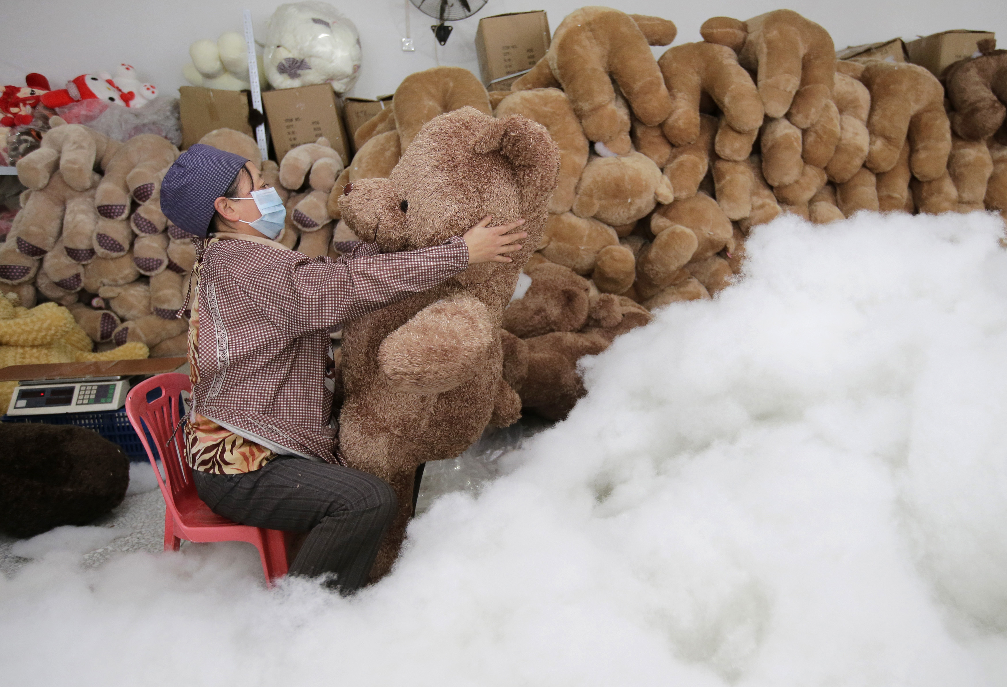 A worker stuffs a toy bear with cotton at a toy factory in Wuhan