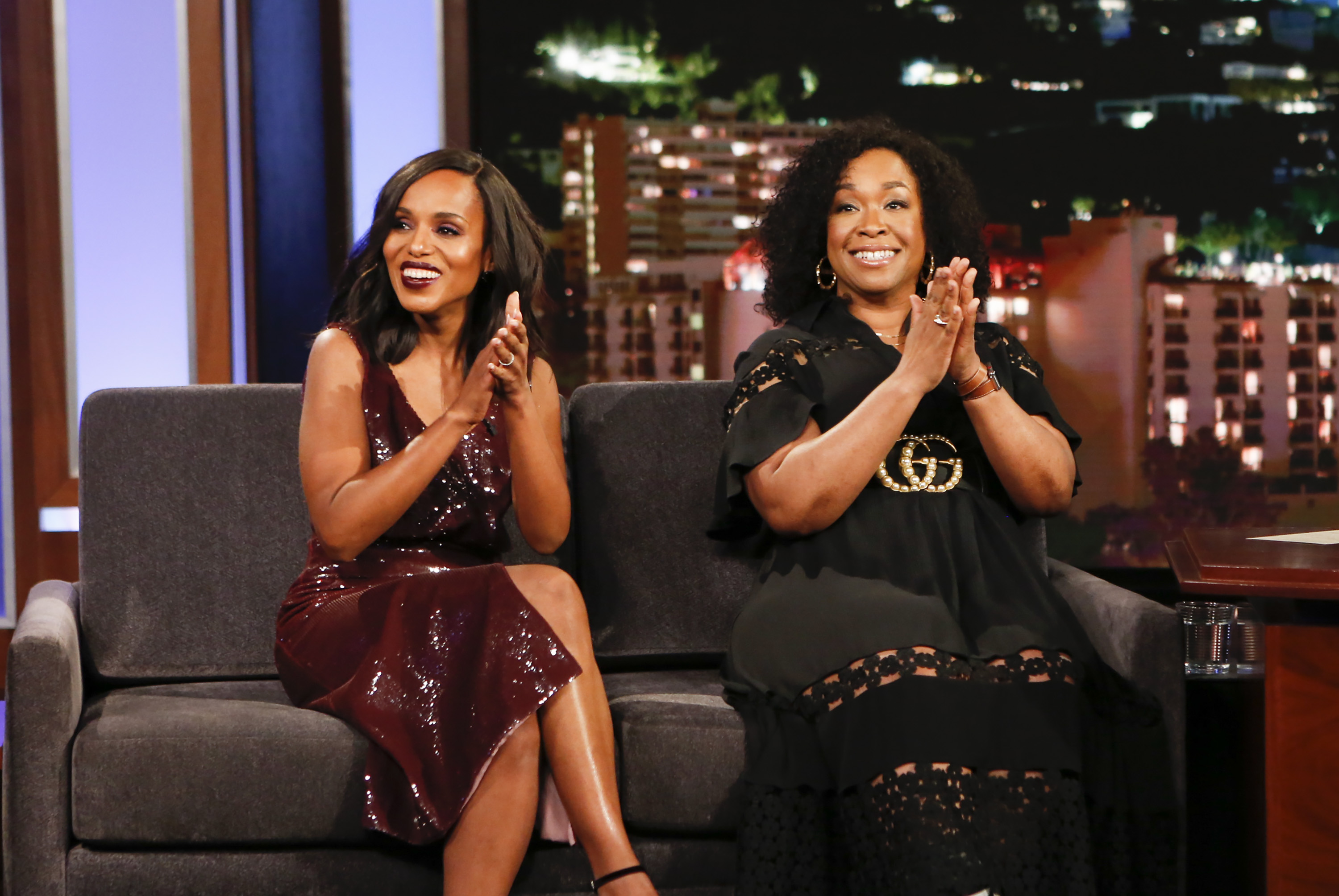 Kerry Washington and Shonda Rhimes sit side by side on a couch, clapping and smiling.