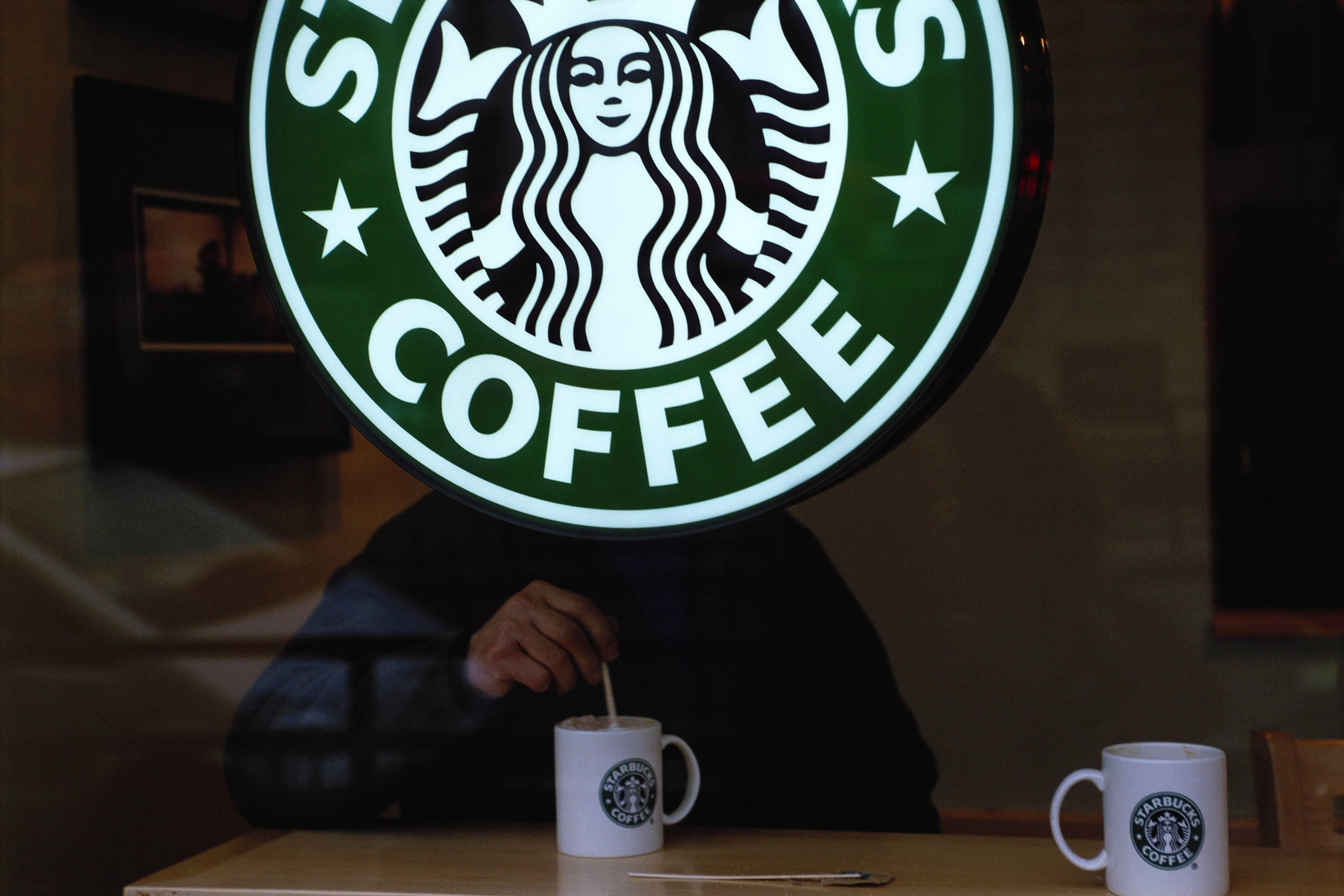 Customer Behind Starbucks Sign in London