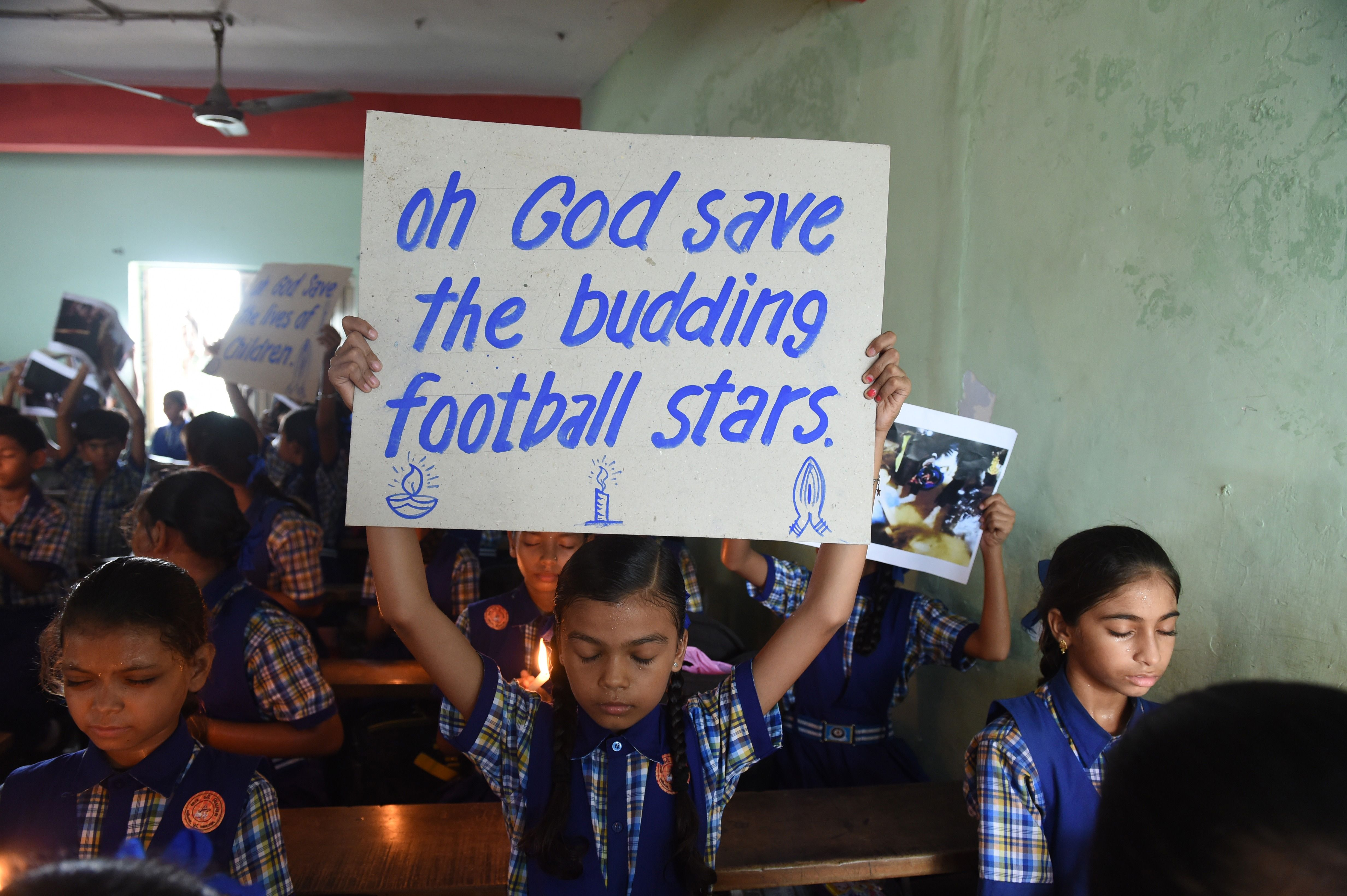 "a boy holds a sign that reads ""oh God save the budding football stars"""