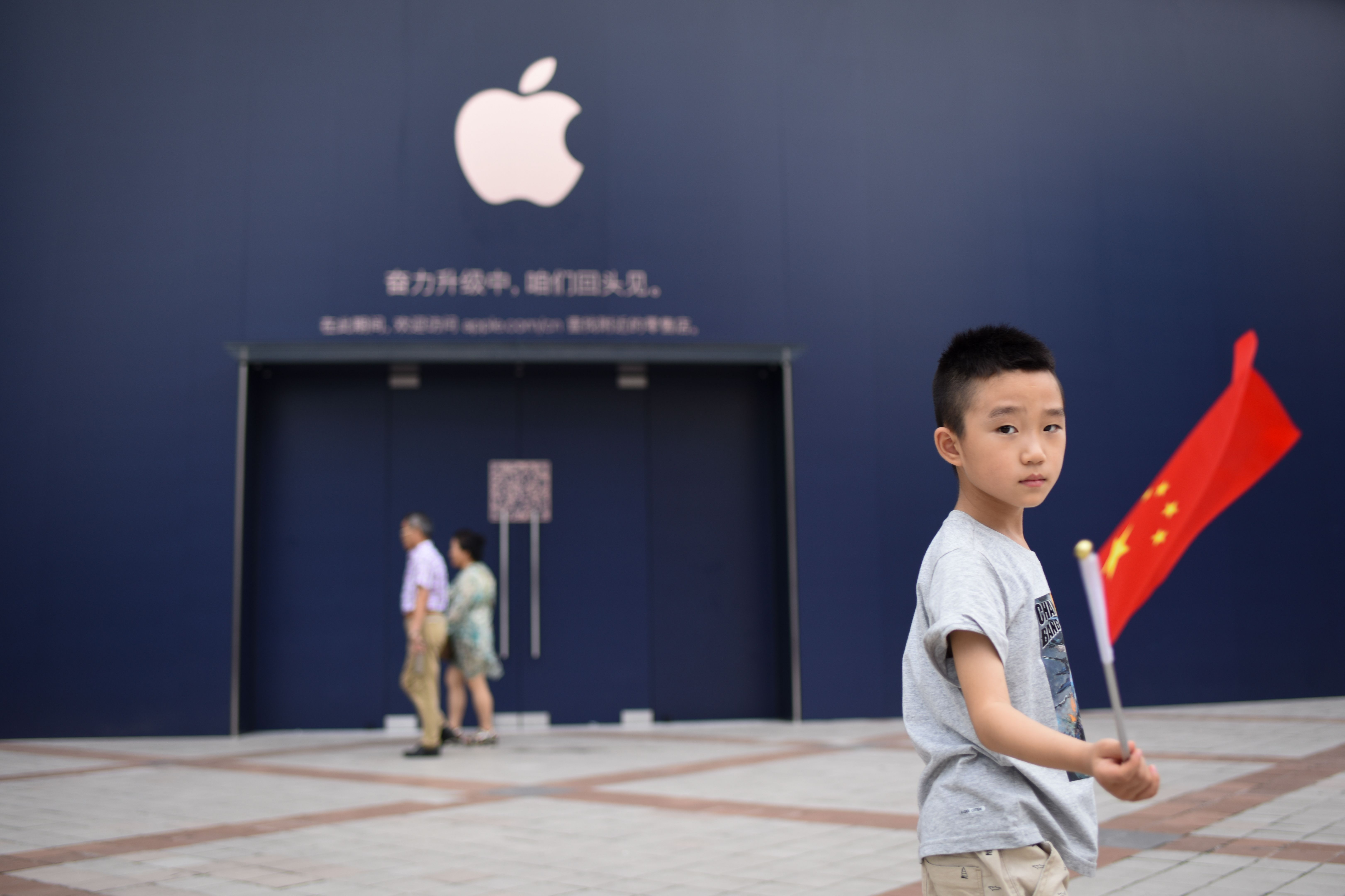 A boy holds a Chinese flag as he walks past an Apple Store undergoing renovation in Beijing on July 18, 2018.