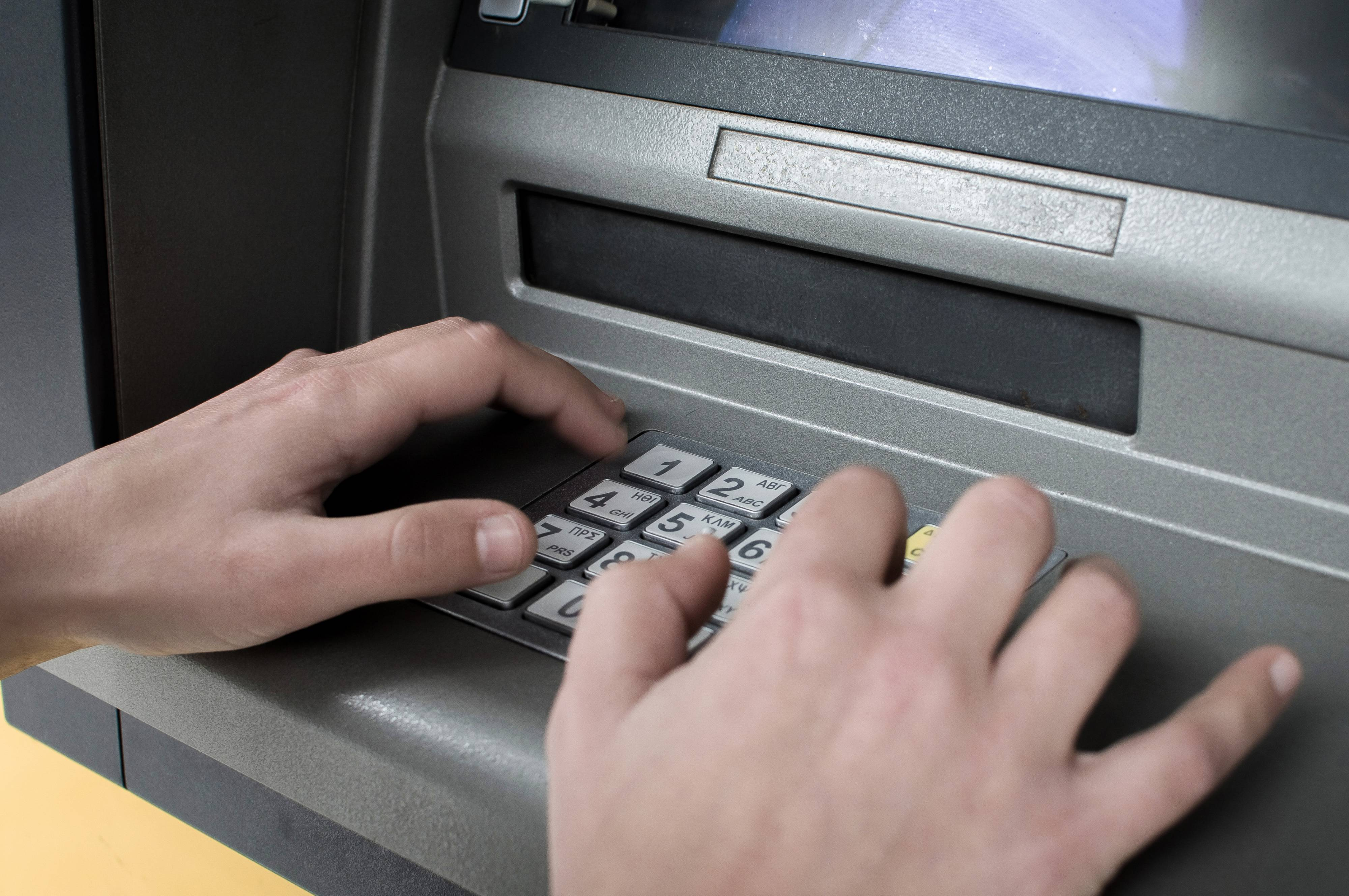 A woman seen typing in the pin on an ATM.People withdrawing