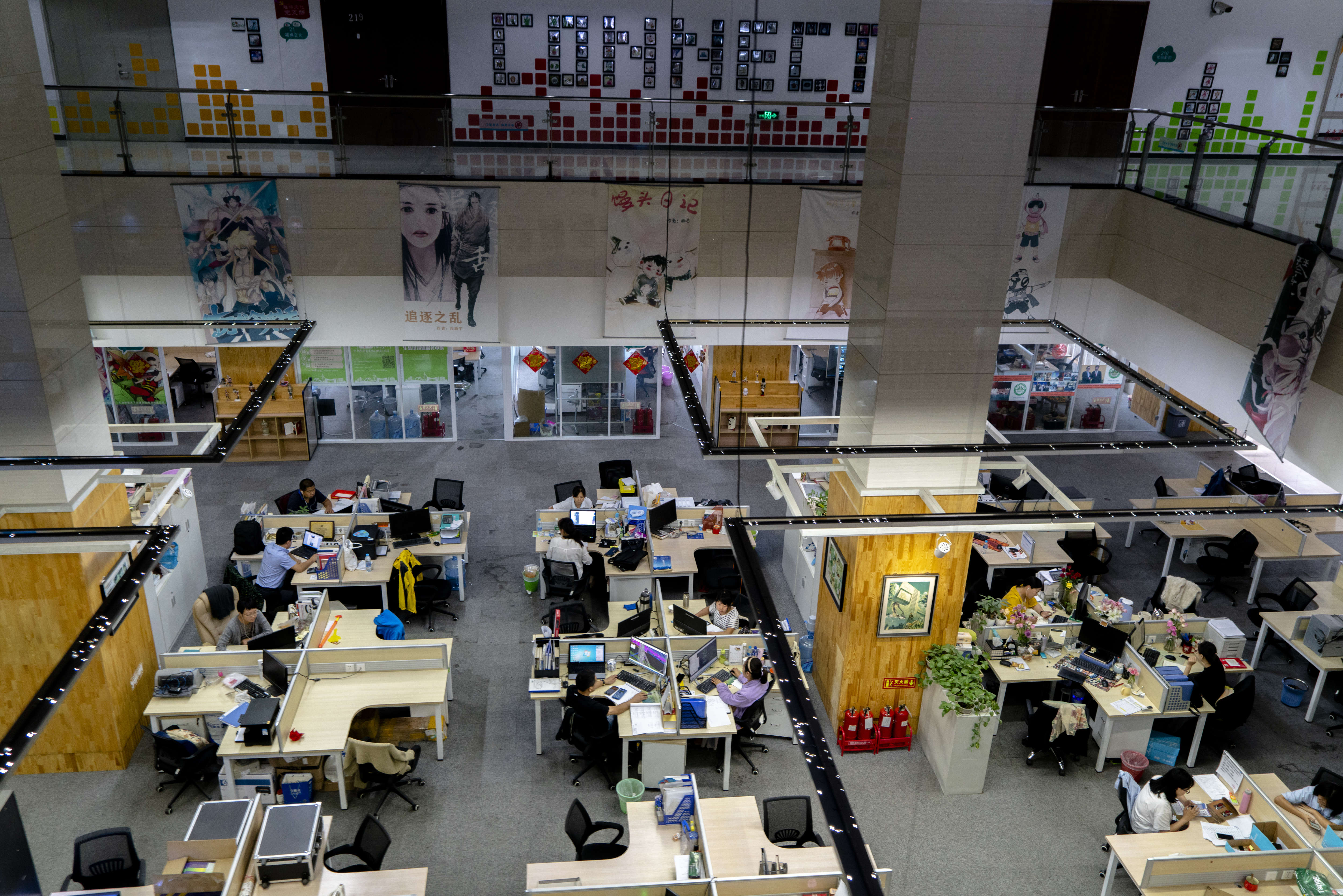 Young people are working in an open office space, which is a