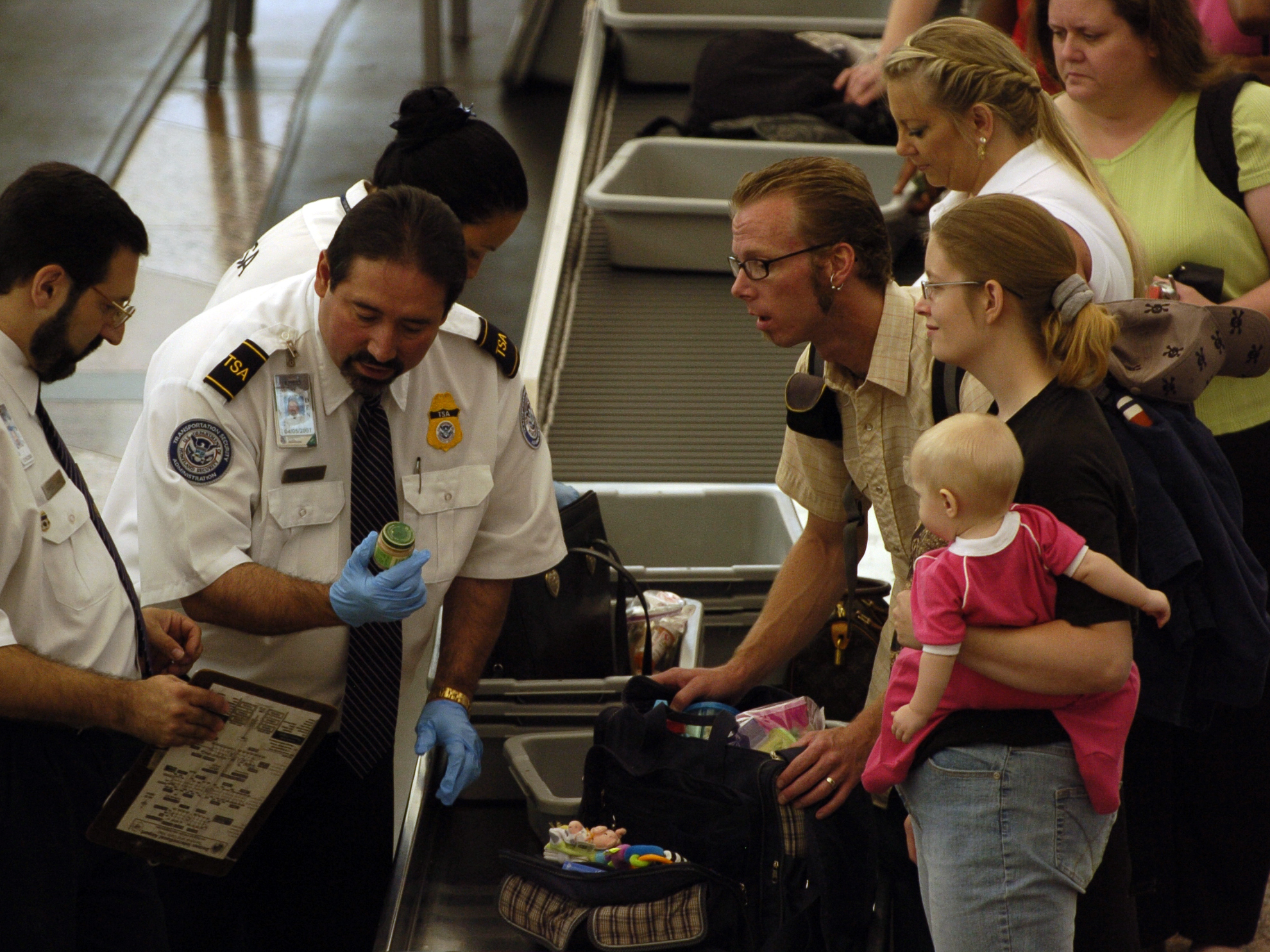 Transportation Security Administration screeners examine and then confiscate bottles of baby food from the carry-on luggage of travelers prior to a flight from Denver International Airport, Thursday, Aug. 10, 2006, in Denver. The airport experienced long