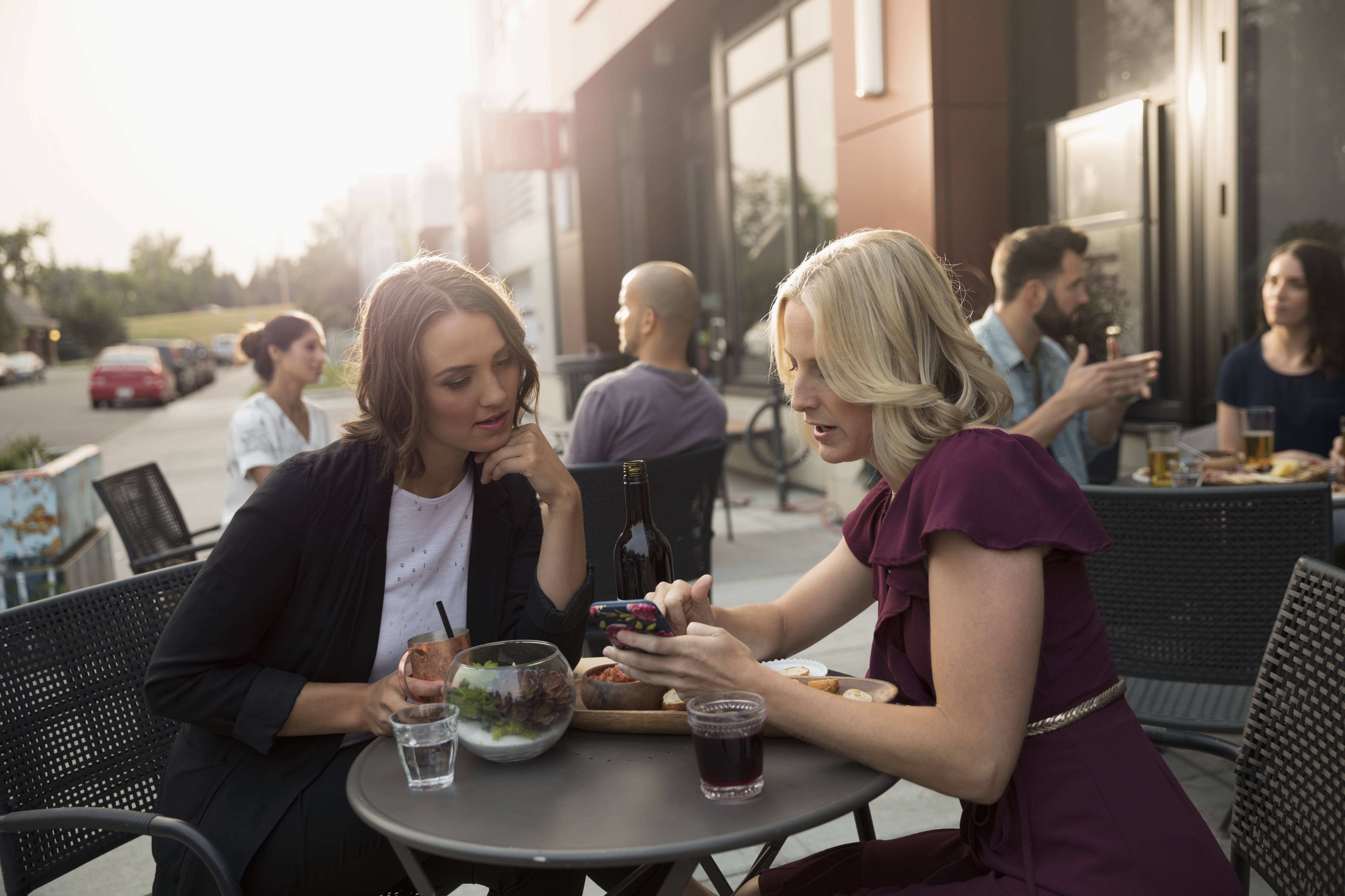 Women friends enjoying wine and cocktail, texting with cell phone at sidewalk cafe