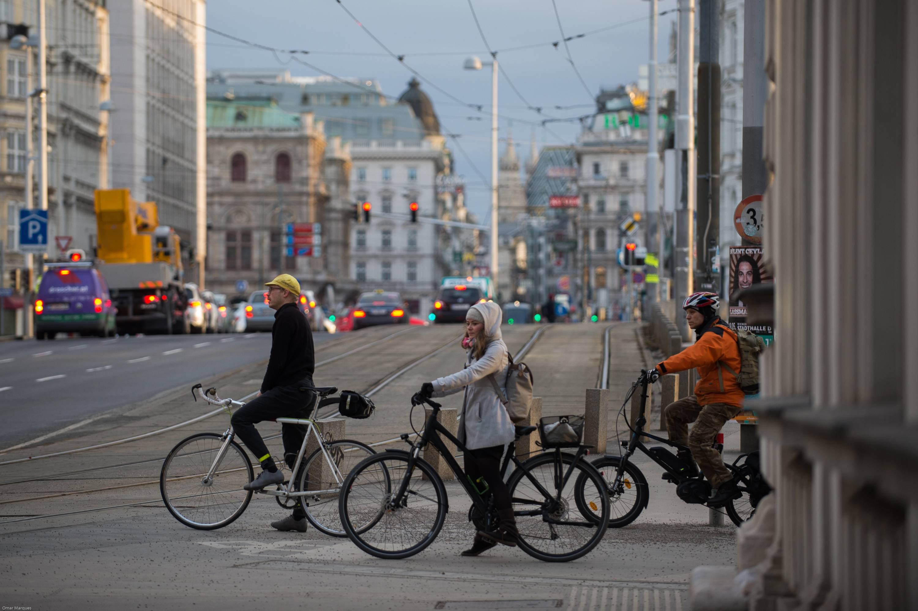 People seen on bicycles as they wait to cross the road in