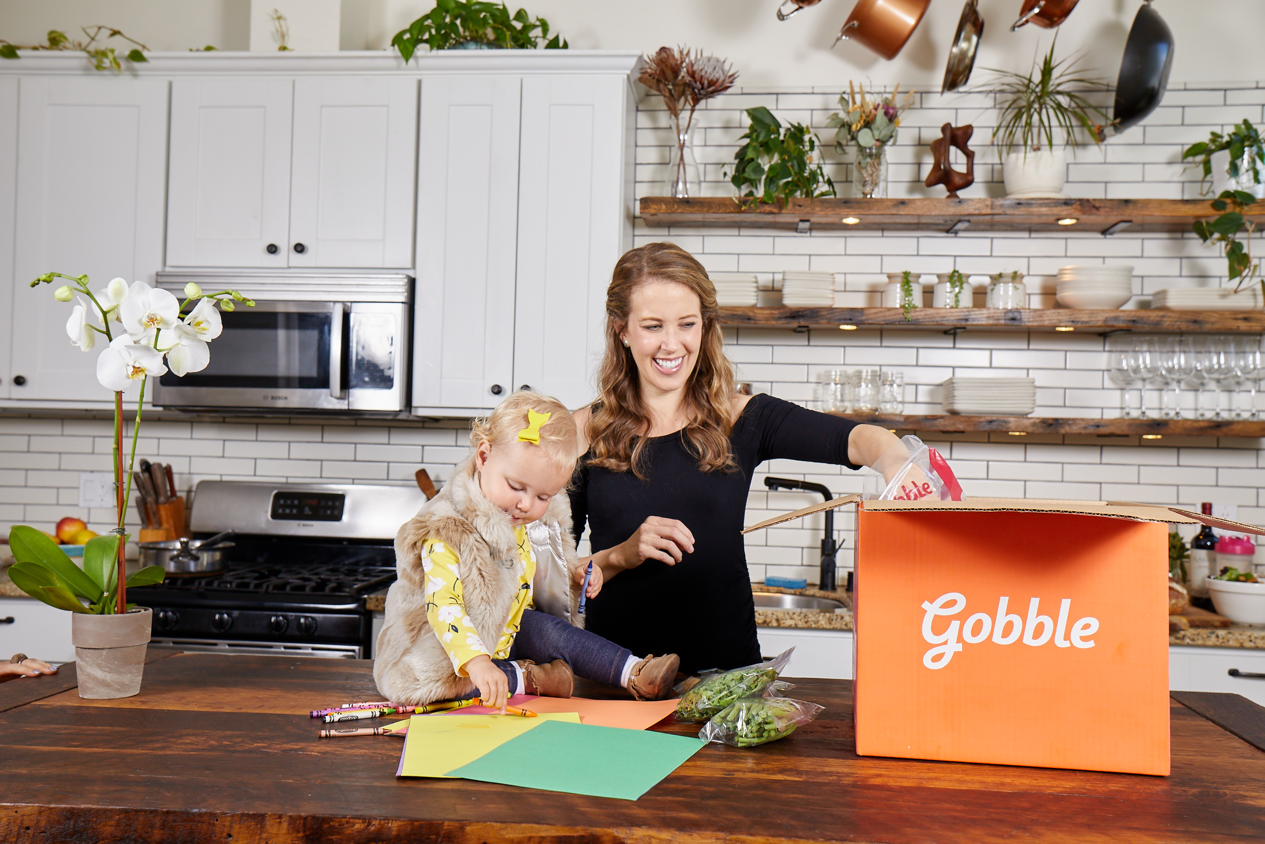 A woman opens a Gobble meal kit box while her young daughter sits on the counter and watches