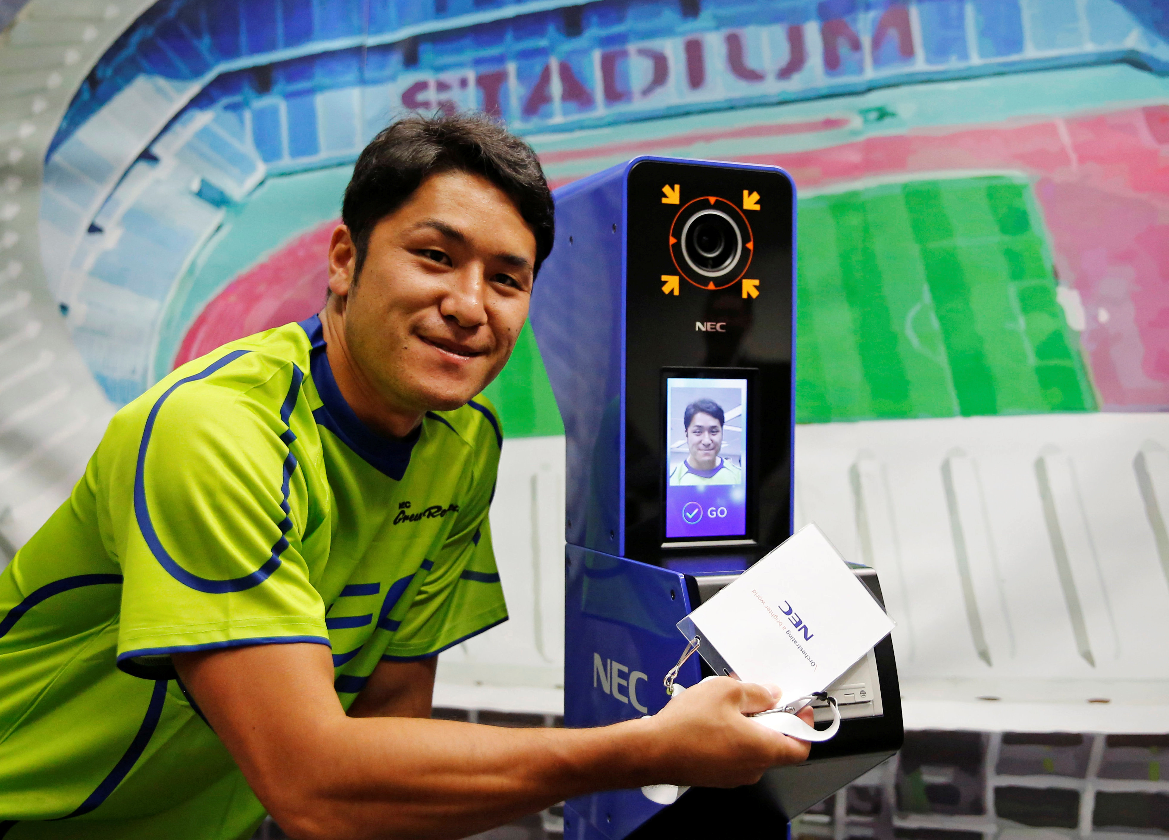 NEC Green Rockets' rugby player Teruya Goto poses with the face recognition system for Tokyo 2020 Olympics and Paralympics, which is developed by NEC corp, during its demonstration in Tokyo