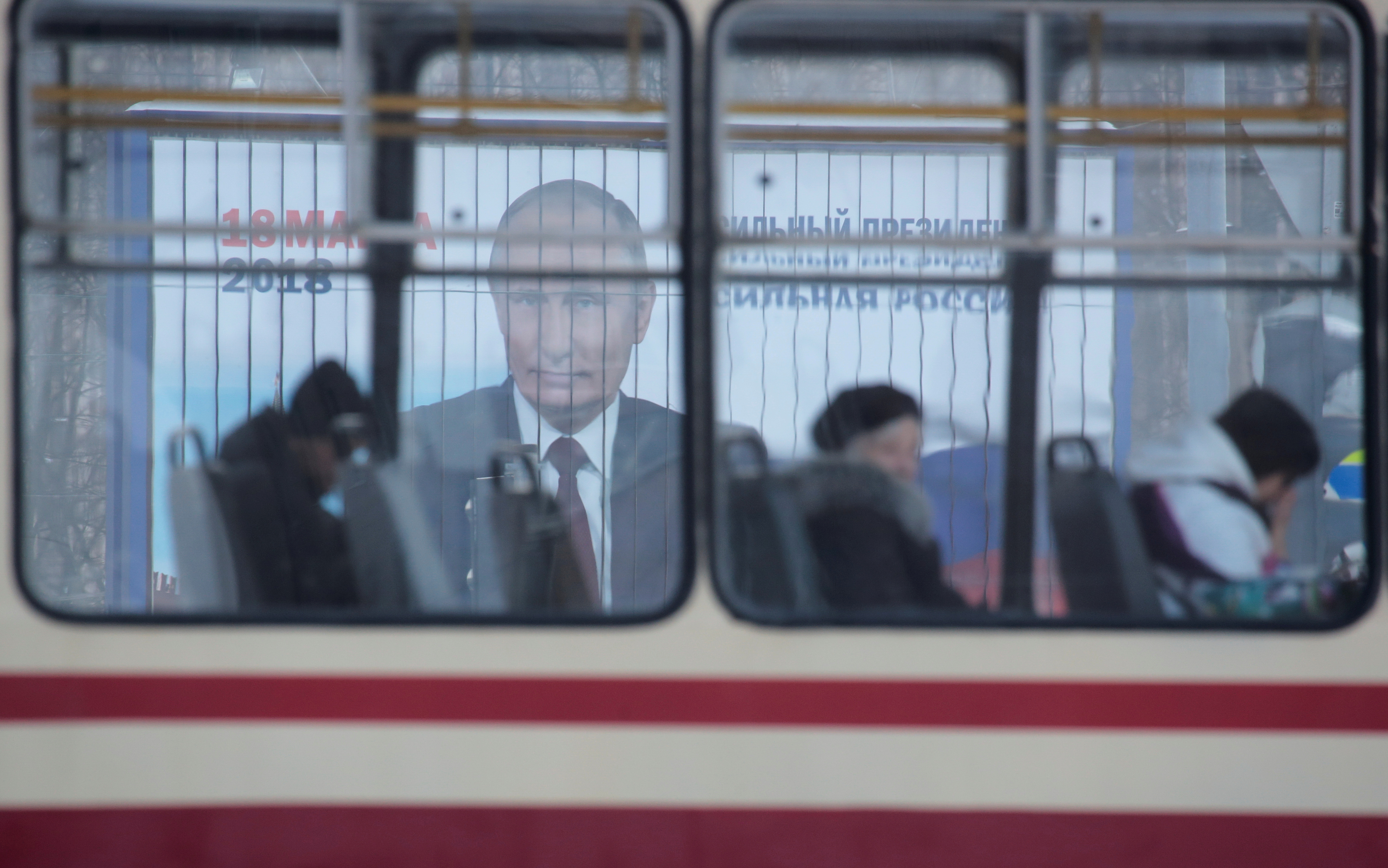 People ride a tram past a board, which advertises the campaign of Russian President Putin ahead of the upcoming presidential election, on a street in St. Petersburg