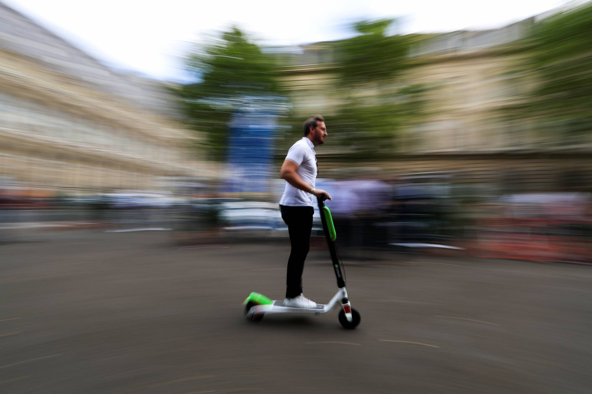 A man rides a dock-free electric scooter Lime-S by California-based bicycle sharing service Lime during a presentation of new alternative urban mobility options at Paris city hall