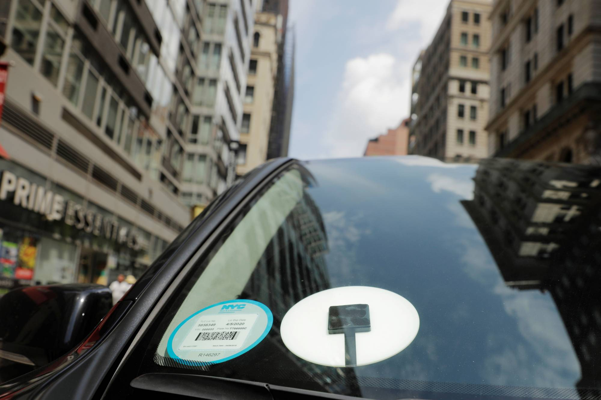 A car with an Uber logo on it drives down the street in New York